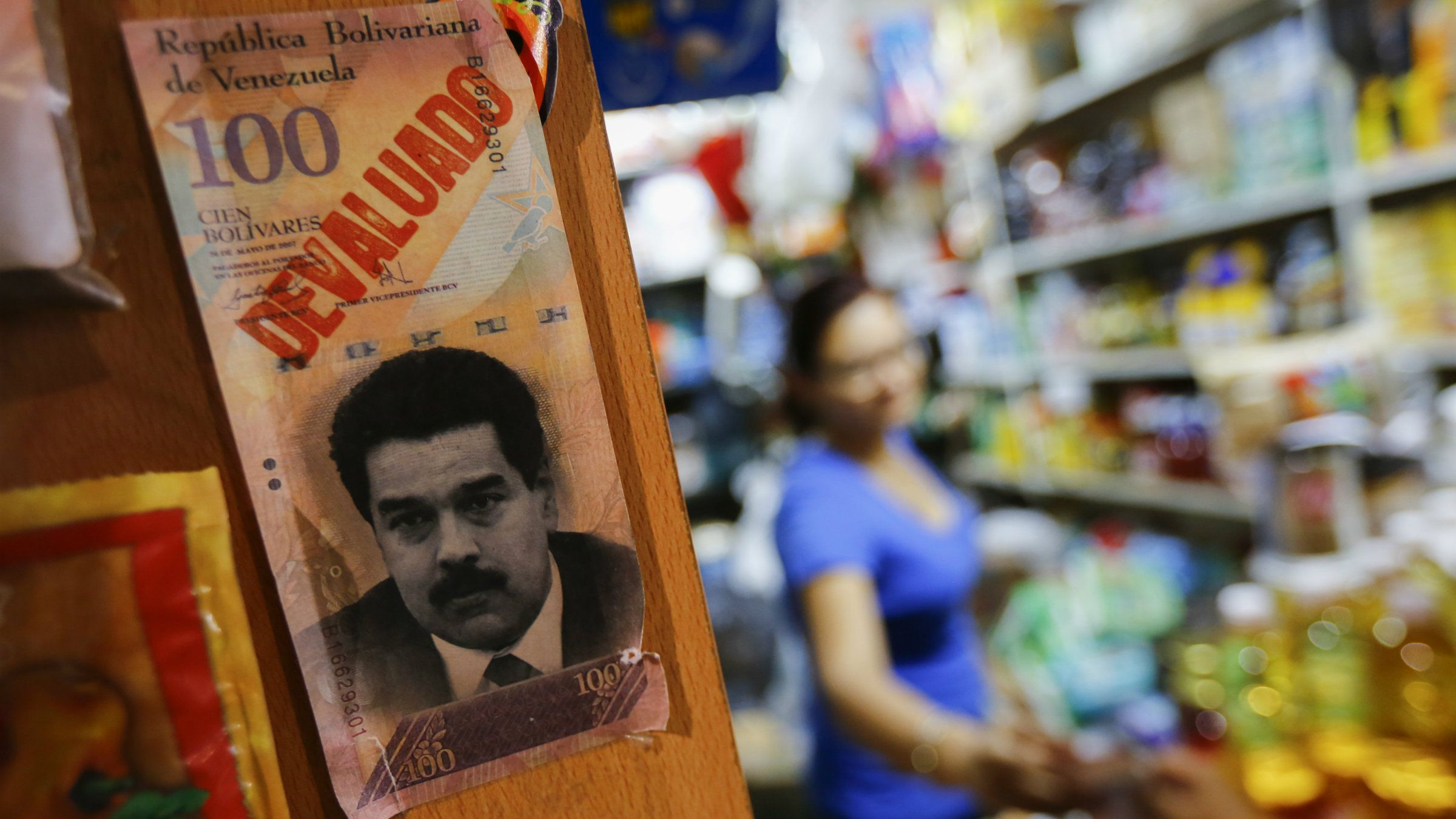 """A sample bank note with the face of Venezuela's President Nicolas Maduro and the word """"devaluated"""" is seen at a market in Caracas ."""