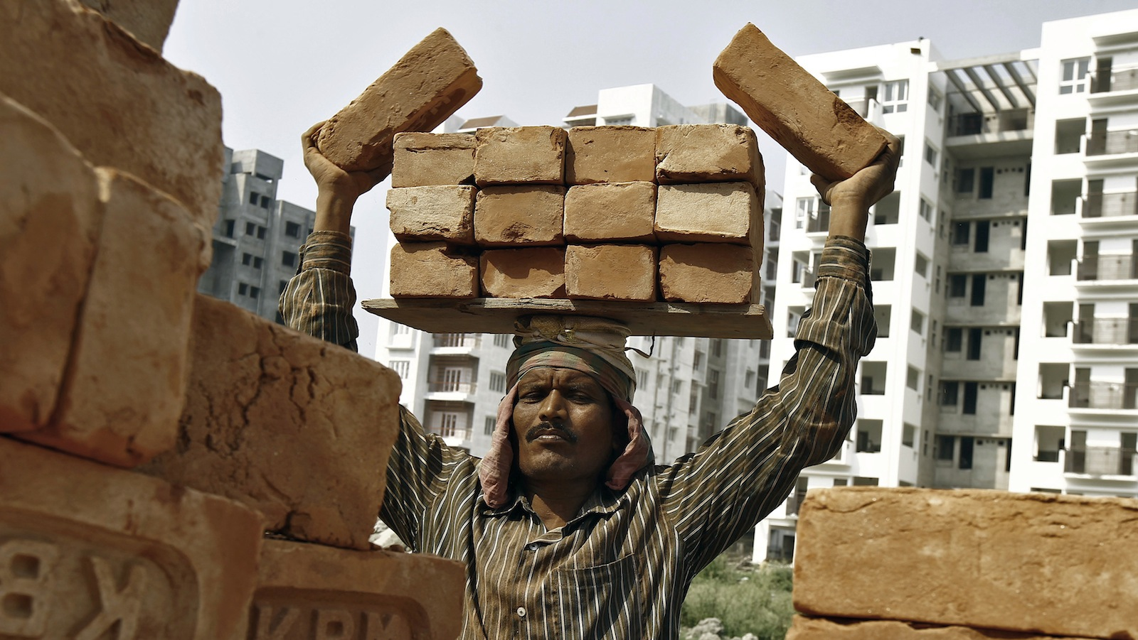 A labourer stacks bricks on his head at the construction site of a residential complex in Kolkata February 28, 2015. India's Finance Minister Arun Jaitley on Saturday announced a budget aimed at high growth, saying the pace of cutting the fiscal deficit would slow as he seeks to boost investment and ensure that ordinary people benefit.