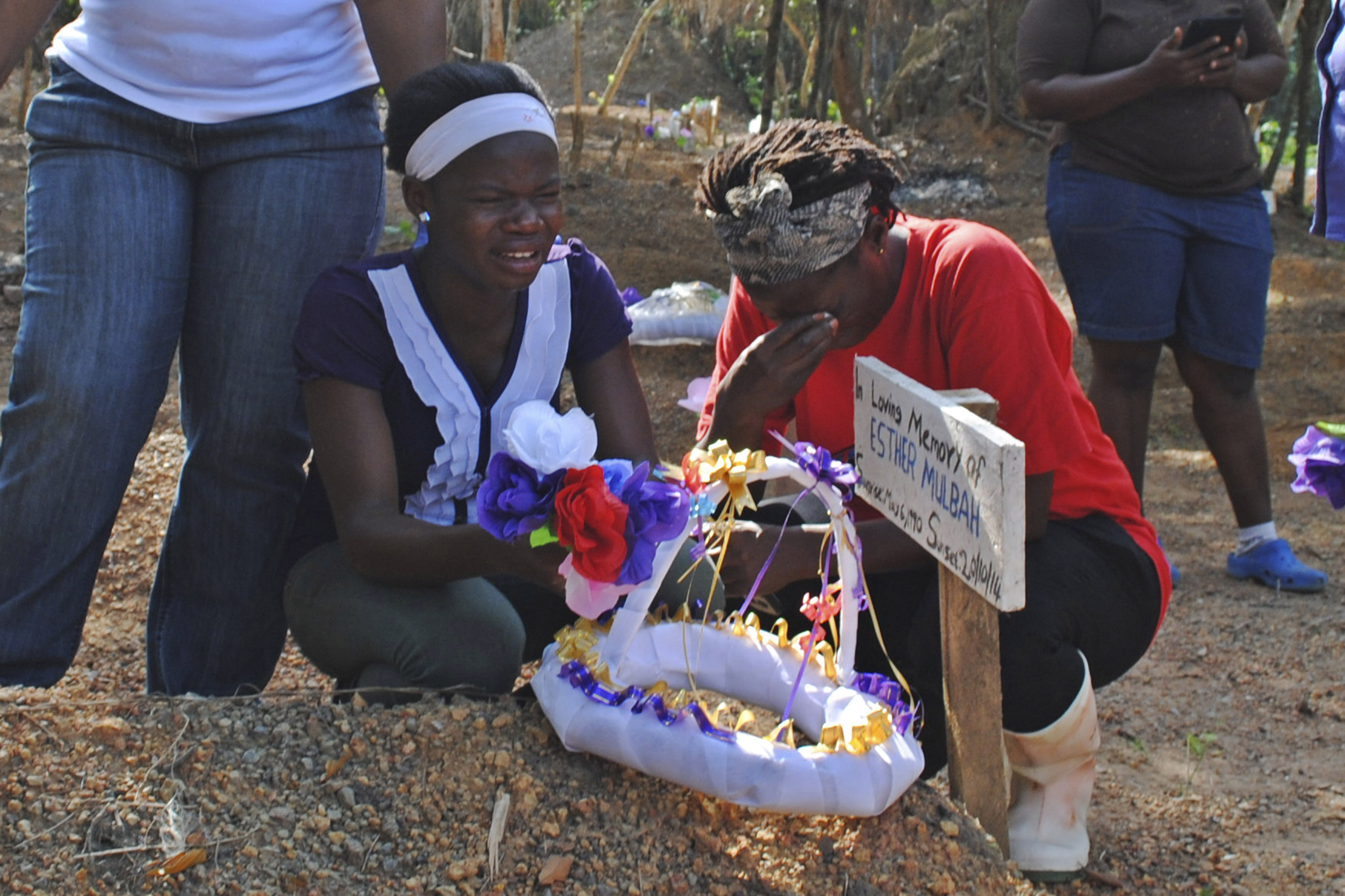 Women weep at the grave of lost relative Esther Mulbah at a cemetery for victims of Ebola virus in Suakoko, Liberia