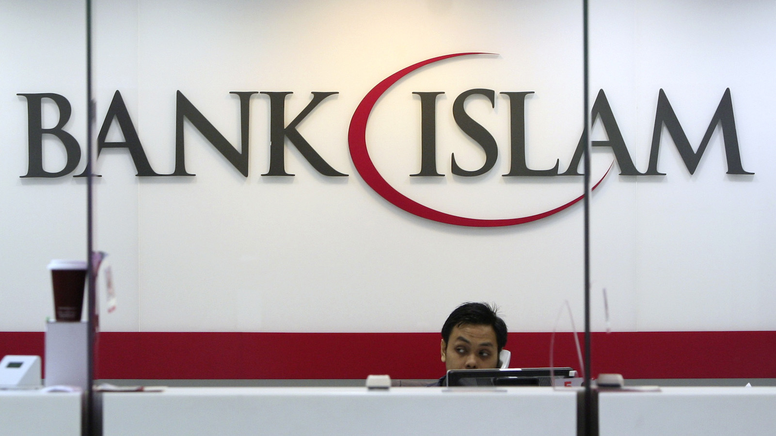 A bank staff speaks on the phone inside the Bank Islam branch office in Shah Alam, outside Kuala Lumpur November 6, 2013. London has long been the default centre for international firms to issue sharia-compliant bonds, part of a fast-growing Islamic finance sector that will be worth $2 trillion globally next year, according to consultants Ernst and Young. But it faces a mounting challenge from two centres: Dubai and Kuala Lumpur. The Malaysian capital has a reputation for efficient regulation of Islamic finance and a huge domestic market for local-currency Islamic bonds, which is now starting to attract foreign issuers.
