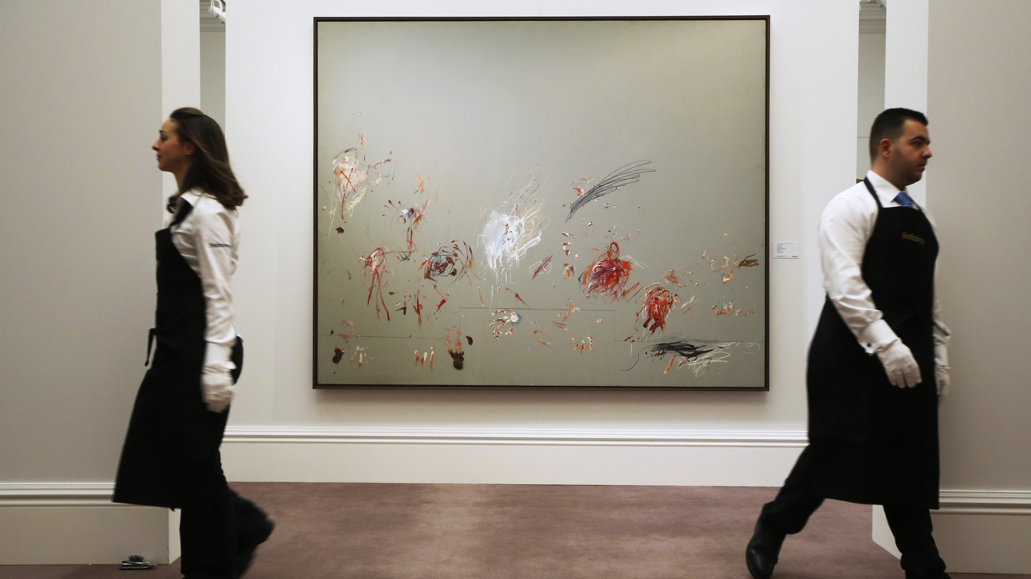 """Employees pose for a photograph with artist Cy Twombly's artwork """"Untitled (Rome)"""" at Sotheby's auction house in London."""