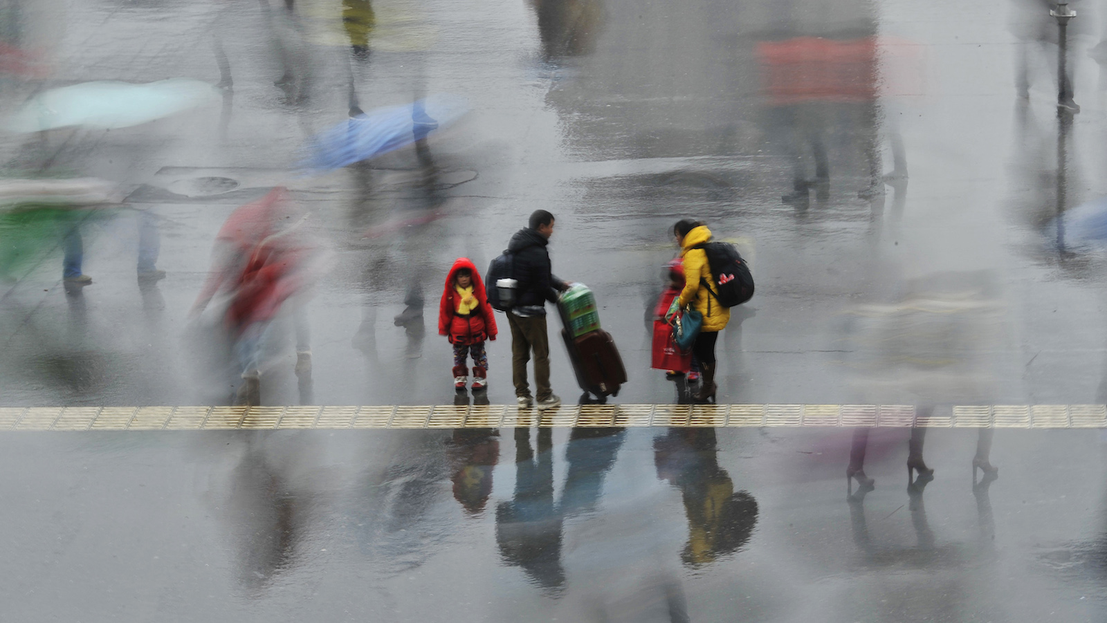 A long exposure photo shows a family standing under the rain outside a railway station in Hefei, Anhui province, February 6, 2014. According to Xinhua News Agency, migrants headed back to work after family reunions at their hometowns during the Chinese lunar New Year holiday.