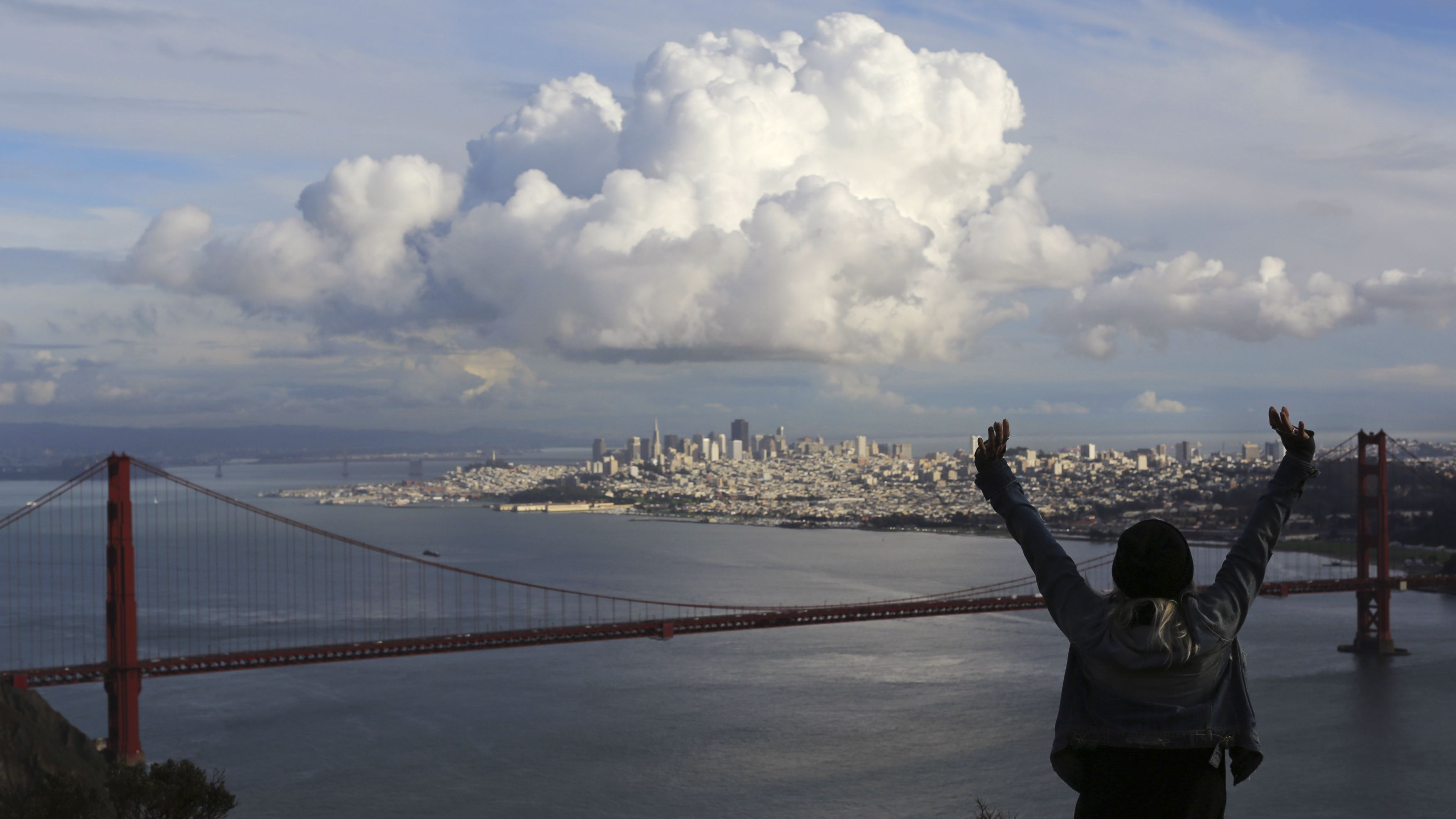 A visitor to the Marin Headlands reacts while looking out over the Golden Gate Bridge and skyline of San Francisco, as a large cloud gathers over the city, December 12, 2014. A major storm pummeled California and the Pacific Northwest with heavy rain and high winds on Thursday, killing one man, knocking out power to tens of thousands of homes, disrupting flights and prompting schools to close. REUTERS/Robert Galbraith (UNITED STATES - Tags: ENVIRONMENT TRAVEL CITYSCAPE) - RTR4HU44