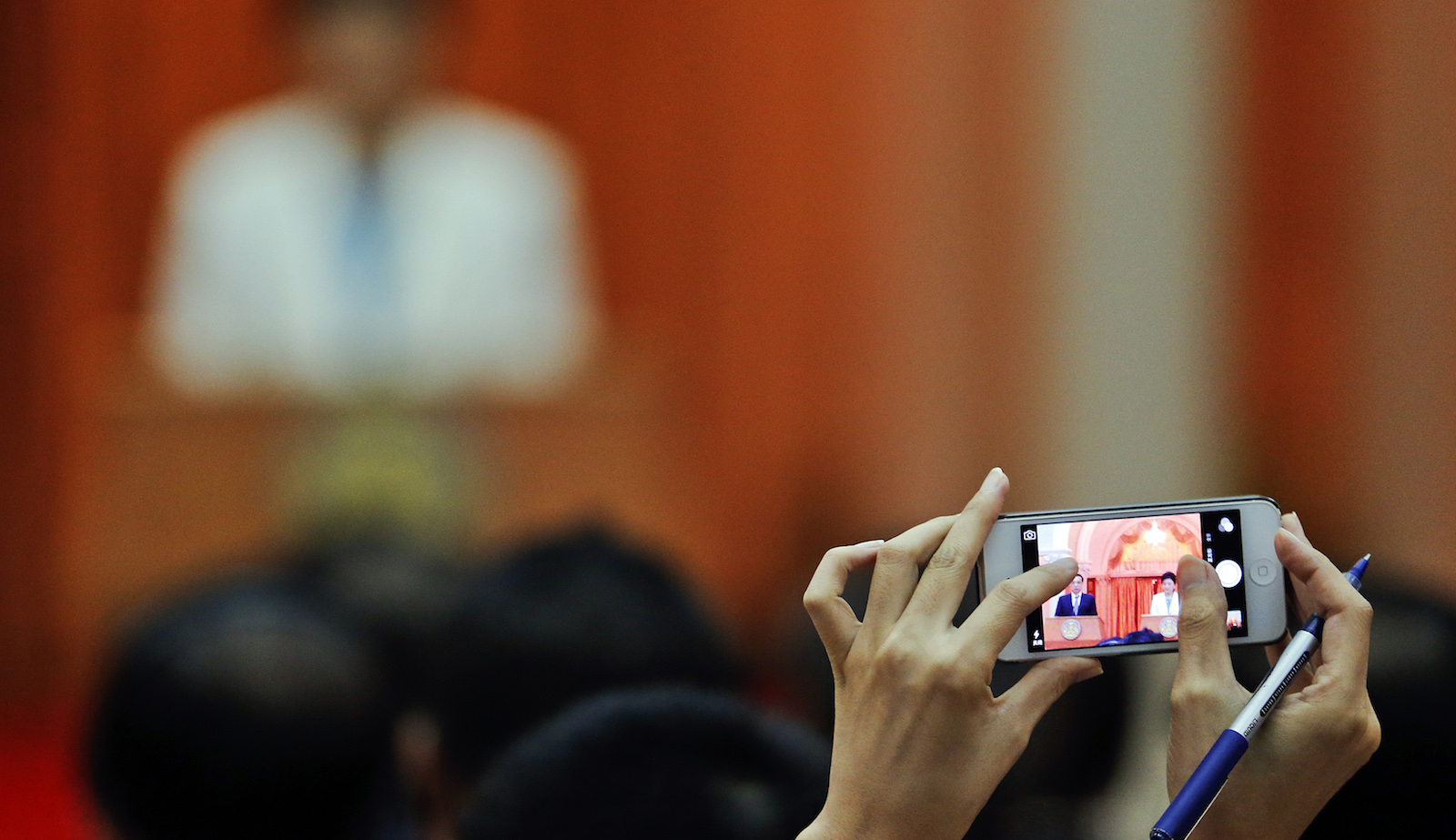 A reporter takes pictures of Thailand's Prime Minister Yingluck Shinawatra and China's Premier Li Keqiang as they address the press at the government house in Bangkok October 11, 2013.
