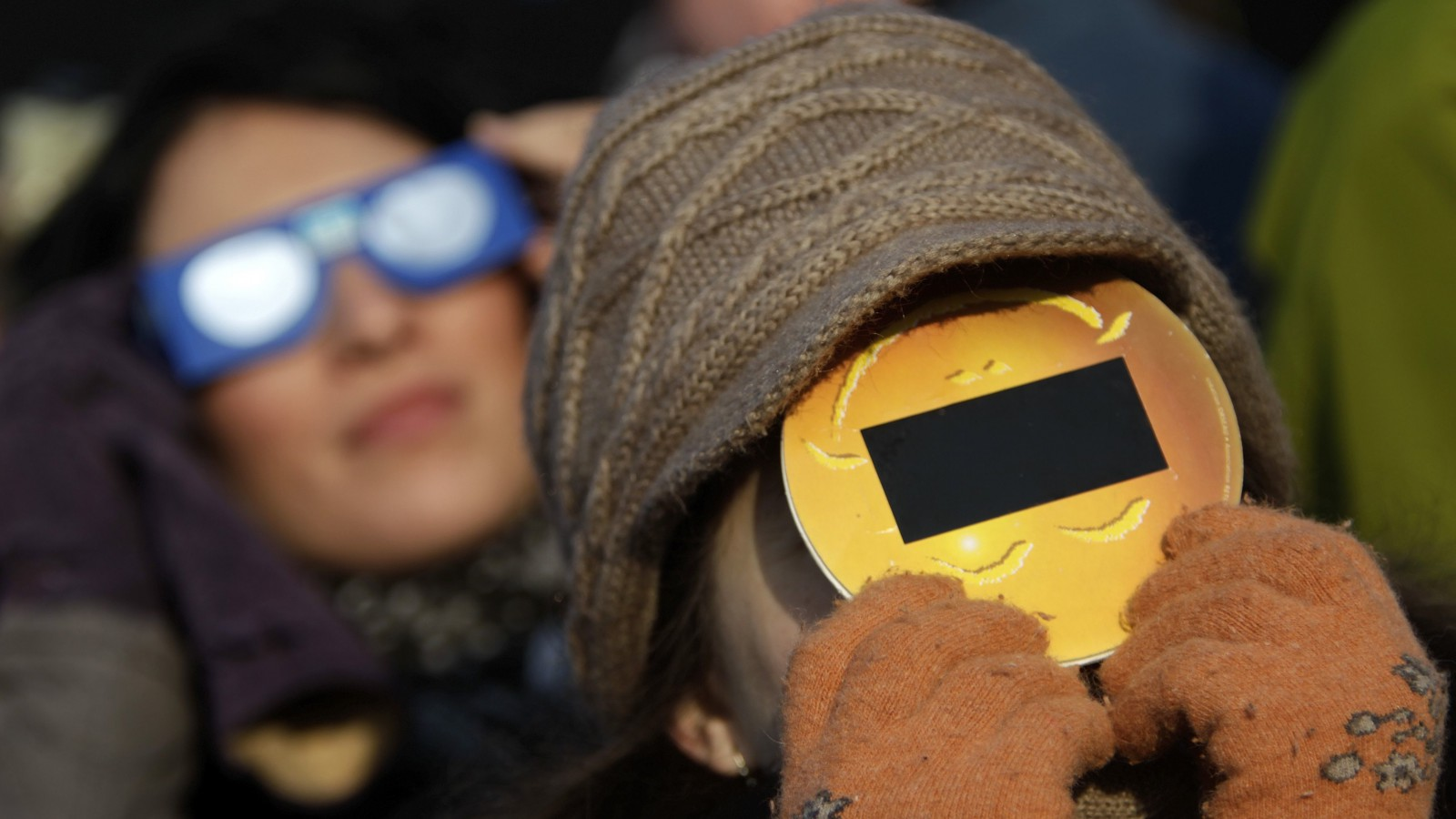 People wear protective eyewear as they look at a partial solar eclipse in Bucharest January 4, 2011. The partial eclipse will be visible near sunrise over most of Europe. REUTERS/Bogdan Cristel (ROMANIA - Tags: ENVIRONMENT) - RTXW746