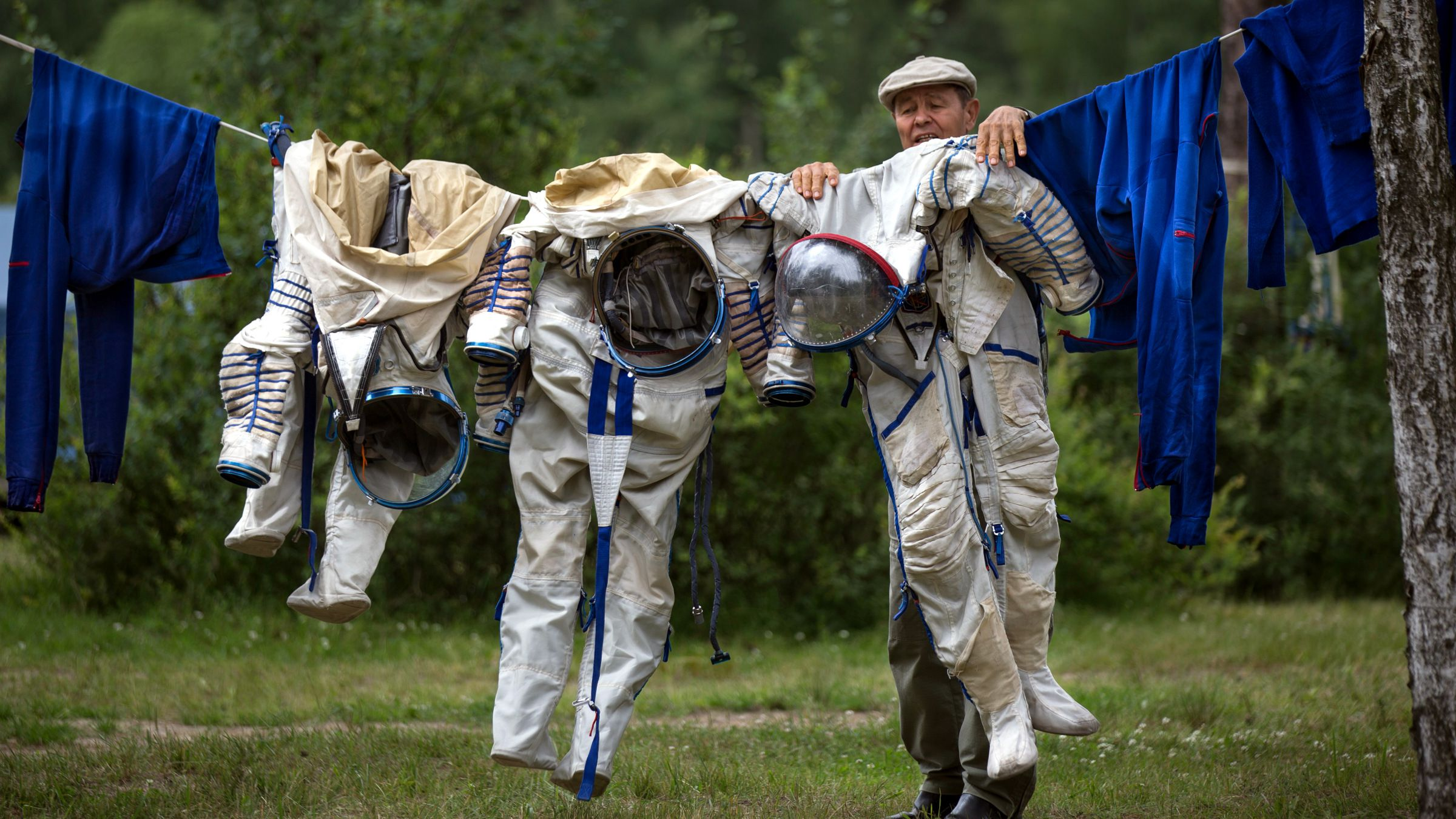 FOR USE AS DESIRED, YEAR END PHOTOS - FILE - An employee of the Russian Space Training Center hangs out space suits to dry of Russian cosmonaut Anatoly Ivanishin, NASA's U.S. flight engineer Kathleen Rubins and Japanese space agency's flight engineer Takuya Onishi after their undergoing training near in Noginsk, 60 km (38 miles) east of Moscow, Russia, Wednesday, July 2, 2014. The training was intended to simulate the capsule landing on water.