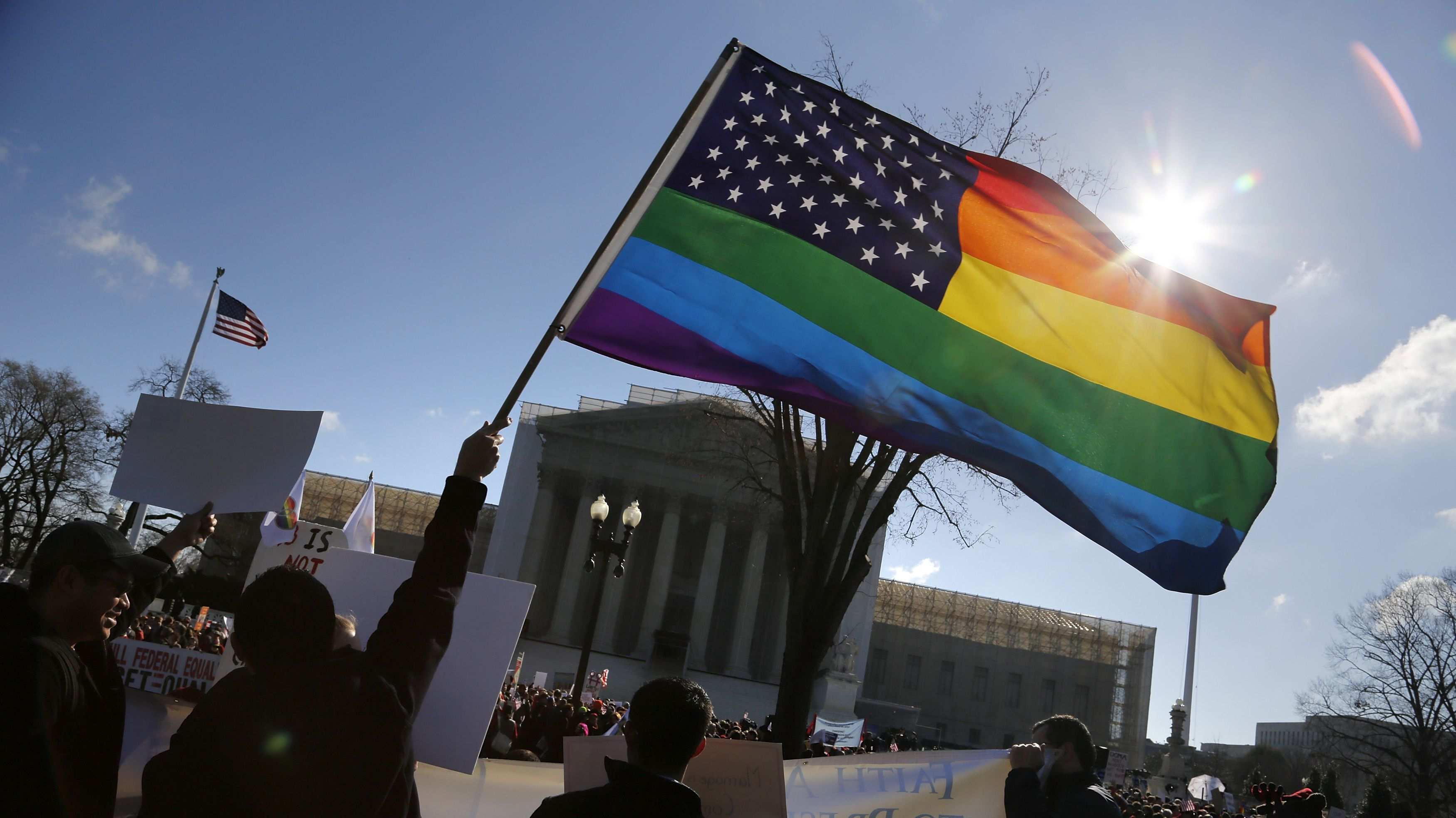 Anti-Proposition 8 protesters wave a rainbow flag in front of the U.S. Supreme Court in Washington, March 26, 2013. Two members of the U.S. Supreme Court, both viewed as potential swing votes on the right of gay couples to marry, raised doubts about California's gay marriage ban on Tuesday as they questioned a lawyer defending the ban. REUTERS/Jonathan Ernst (UNITED STATES - Tags: POLITICS SOCIETY CIVIL UNREST TPX IMAGES OF THE DAY) - RTXXY6A