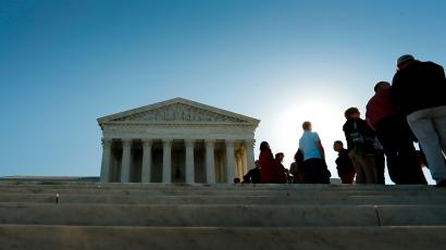 Visitors stand in line to watch arguments on the first day of the new term of the U.S. Supreme Court in Washington October 6, 2014.
