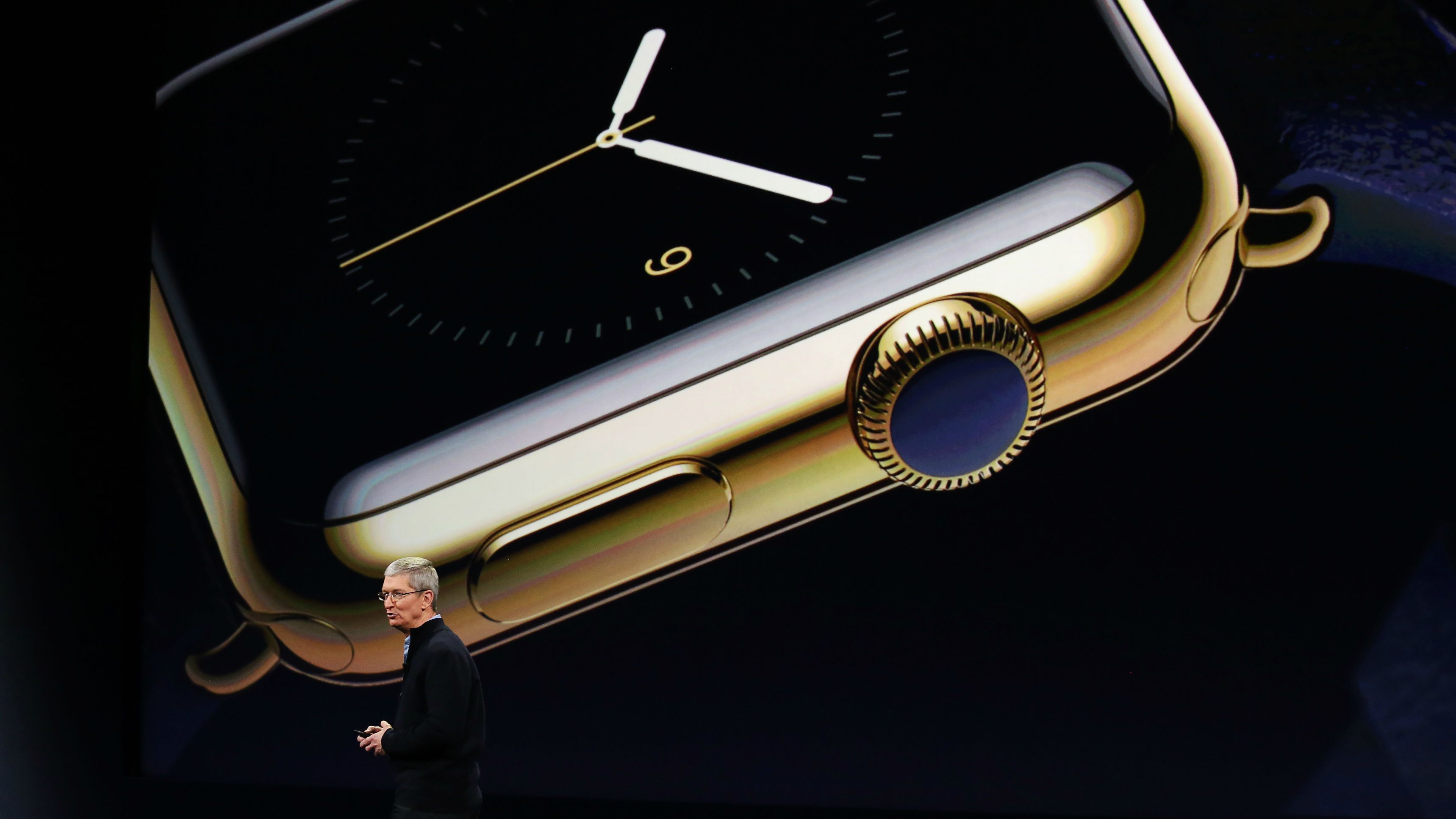 Tim Cook showing gold Apple Watch at company event.