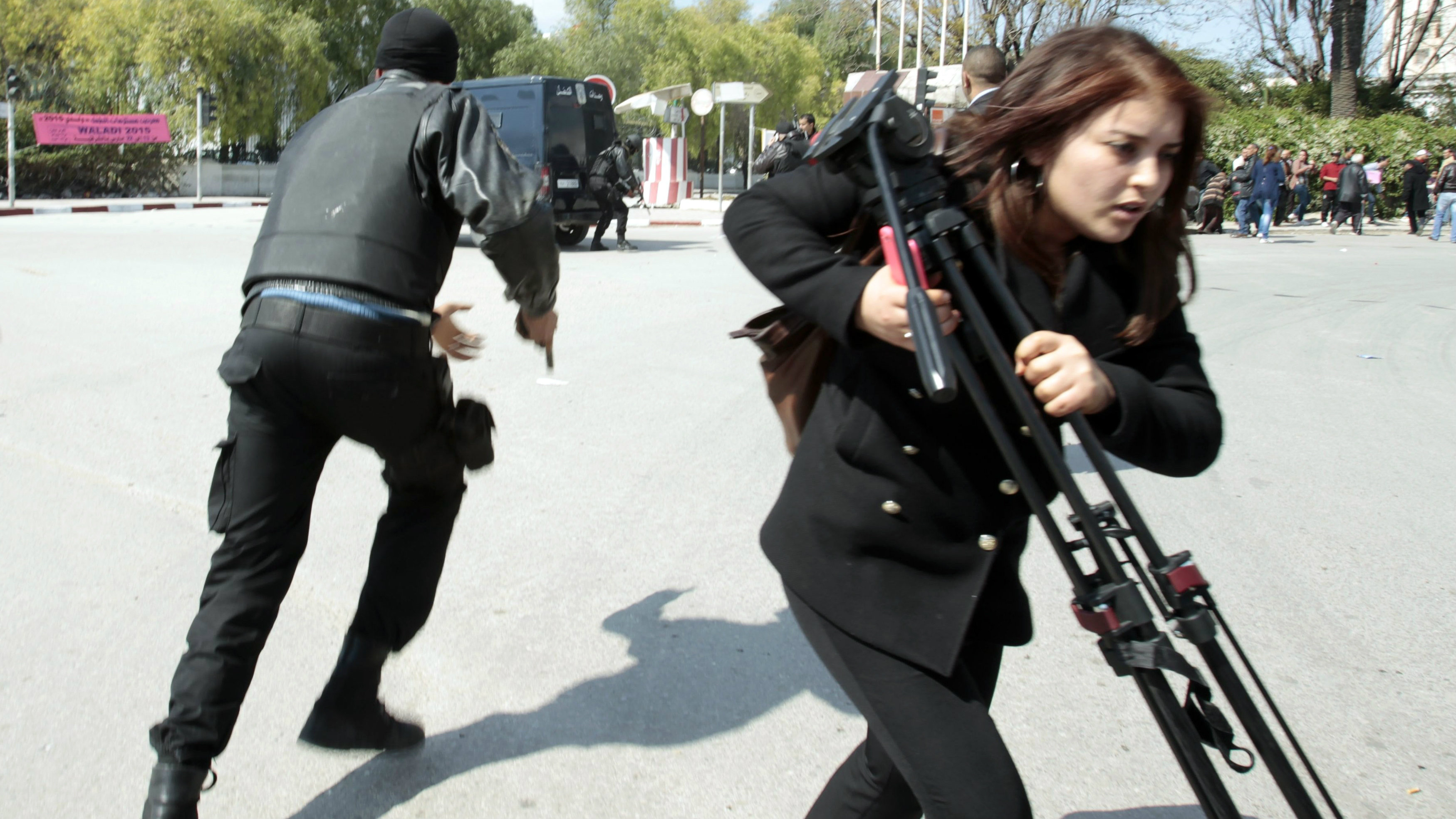 Police officers and a journalist run outside the parliament in Tunis March 18, 2015.