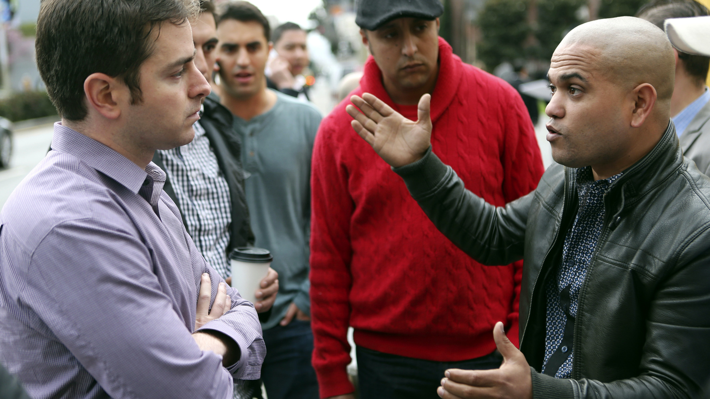 Uber driver Ramsi Reguii (R) expresses his grievances with Uber General Manager Ilya Abyzov during a protest to request for better pay and better communication with the private transportation service company outside Uber's office in San Francisco, California, January 27, 2014
