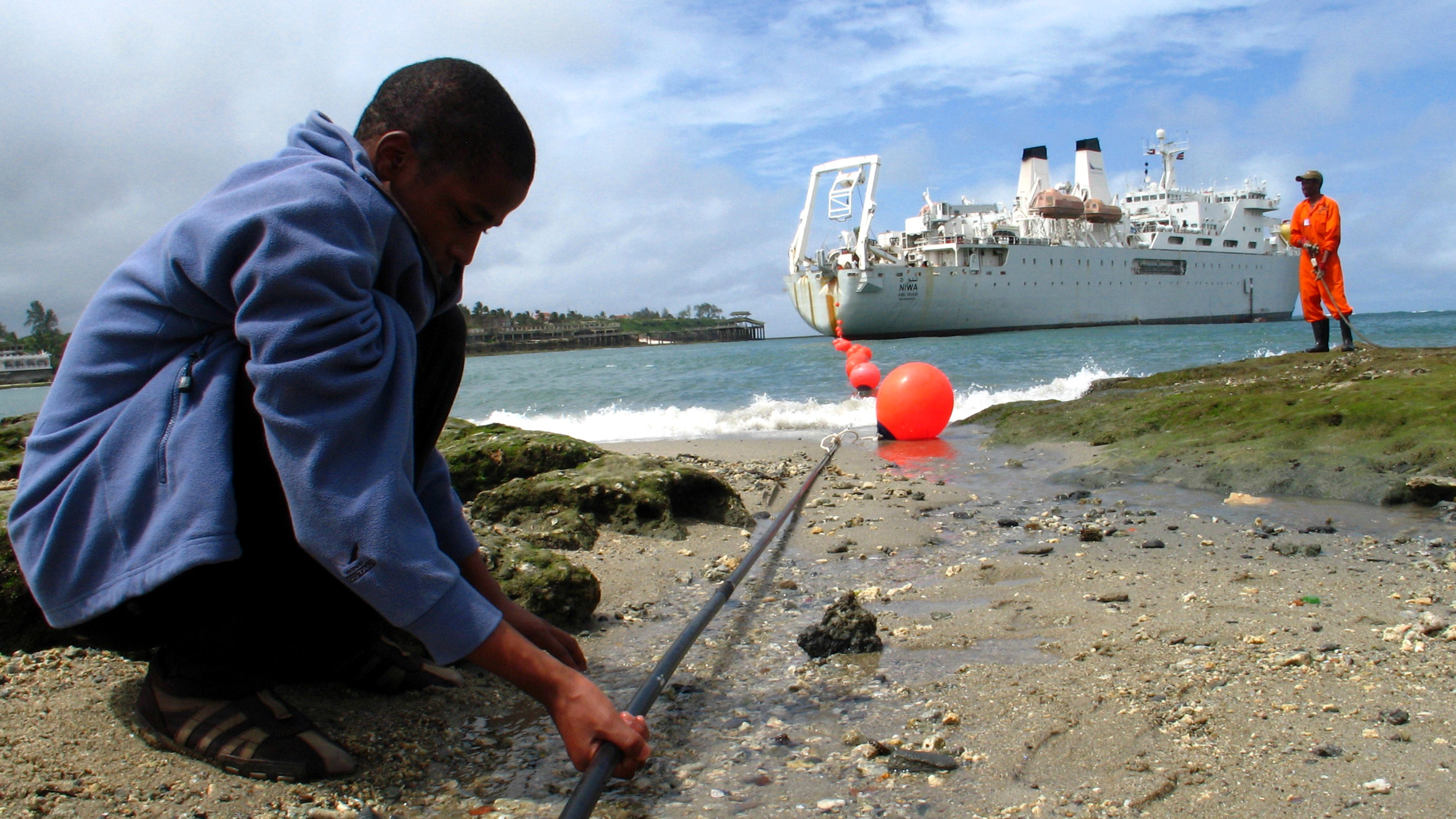 A Kenyan boy looks at the East African Marine Cable (TEAMS) fiber optic cable from the ship Niwa outside the Portuguese built Fort Jesus in the Kenyan coastal city of Mombasa, June 12, 2009. The cable has taken 18 months to reach the Kenyan coast by sea from the Middle East and is set to improve information and communication technology in Africa.
