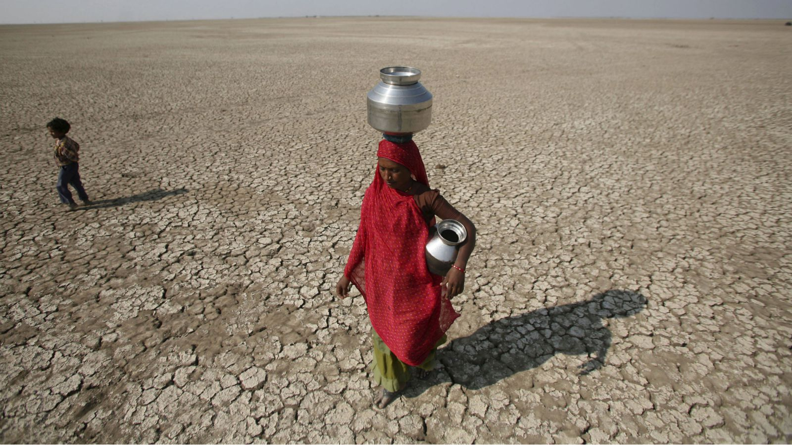 A salt worker carries metal pitchers to collect drinking water in Kharaghodha village, about 120 km (75 miles) west from the western Indian city of Ahmedabad November 7, 2009.