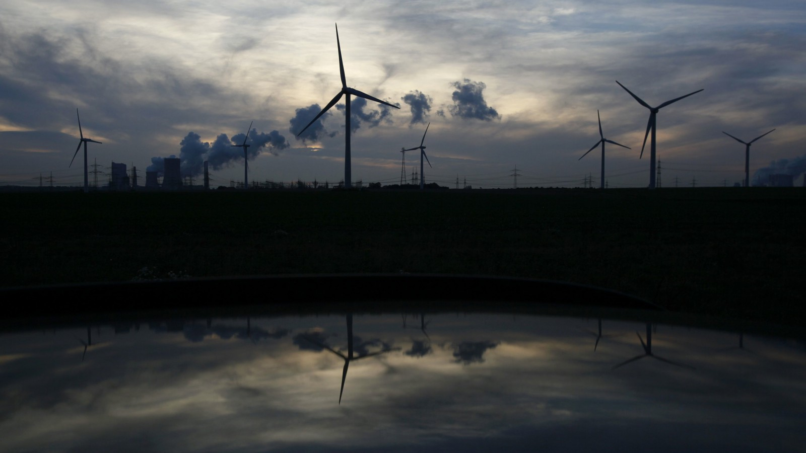 Wind generators and the Niederaussem coal power plant of RWE Power, one of Europe's biggest electricity and gas companies, are reflected in the roof of a car in Rheidt, north-west of Cologne .