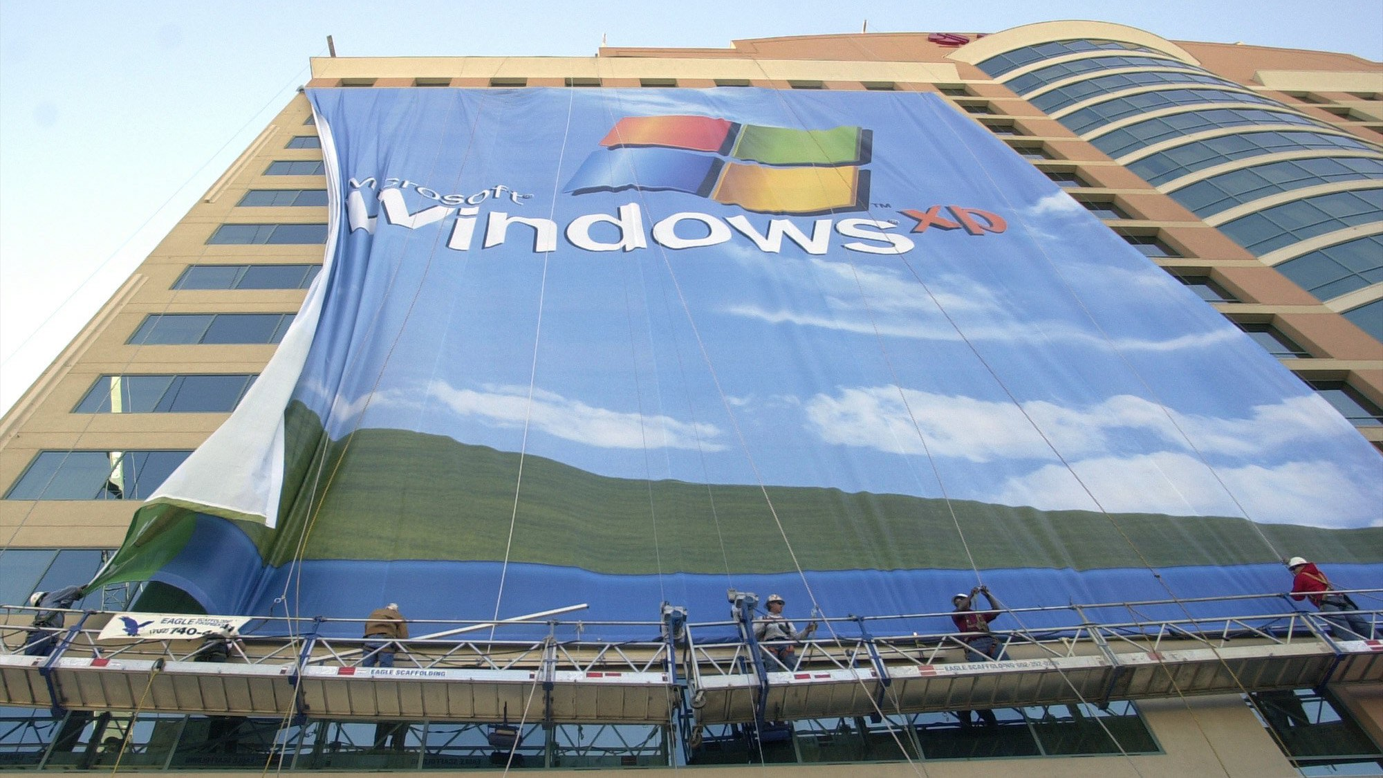 In this Nov. 8 2001 file photo, workers install a 10-story Windows XP banner on a hotel near the Las Vegas Convention Center in Las Vegas. On Tuesday, April 8, 2014, Microsoft will end support for its still popular Windows XP. With an estimated 30 percent of businesses and consumers still using the 12-year-old operating system, the move could put everything from the data of major financial institutions to the identities of everyday people in danger if they don't find a way to upgrade soon. (AP Photo/Joe Cavaretta, File)