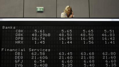 A woman takes some notes as she stands on the gallery over share prize index boards at the German stock exchange in Frankfurt,