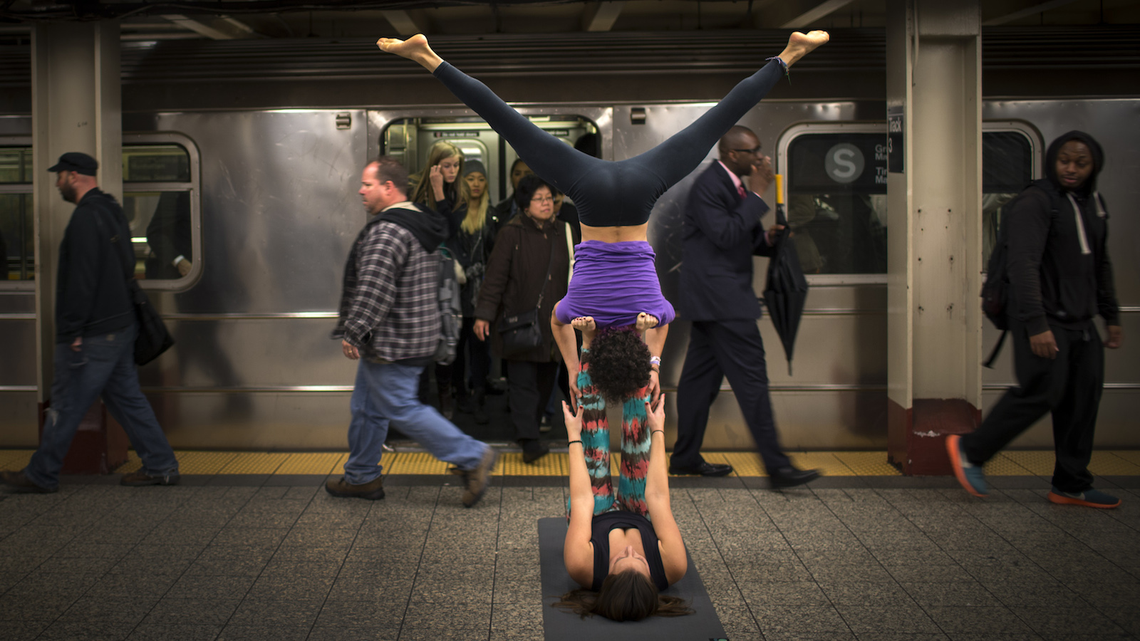 "Lauren Tallody (bottom) and Bassam Kubba (top) practice ""Acro-yoga"", a mixture of yoga and acrobatics on a subway platform at 42nd Street beneath Grand Central station in New York city, October 23, 2014.   REUTERS/Mike Segar   (UNITED STATES - Tags: SOCIETY) - RTR4BD9Q"
