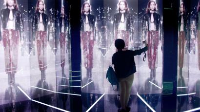 A woman takes photographs of screens showing a fashion show during an exhibition by French luxury brand Louis Vuitton in Beijing on April 9, 2015.