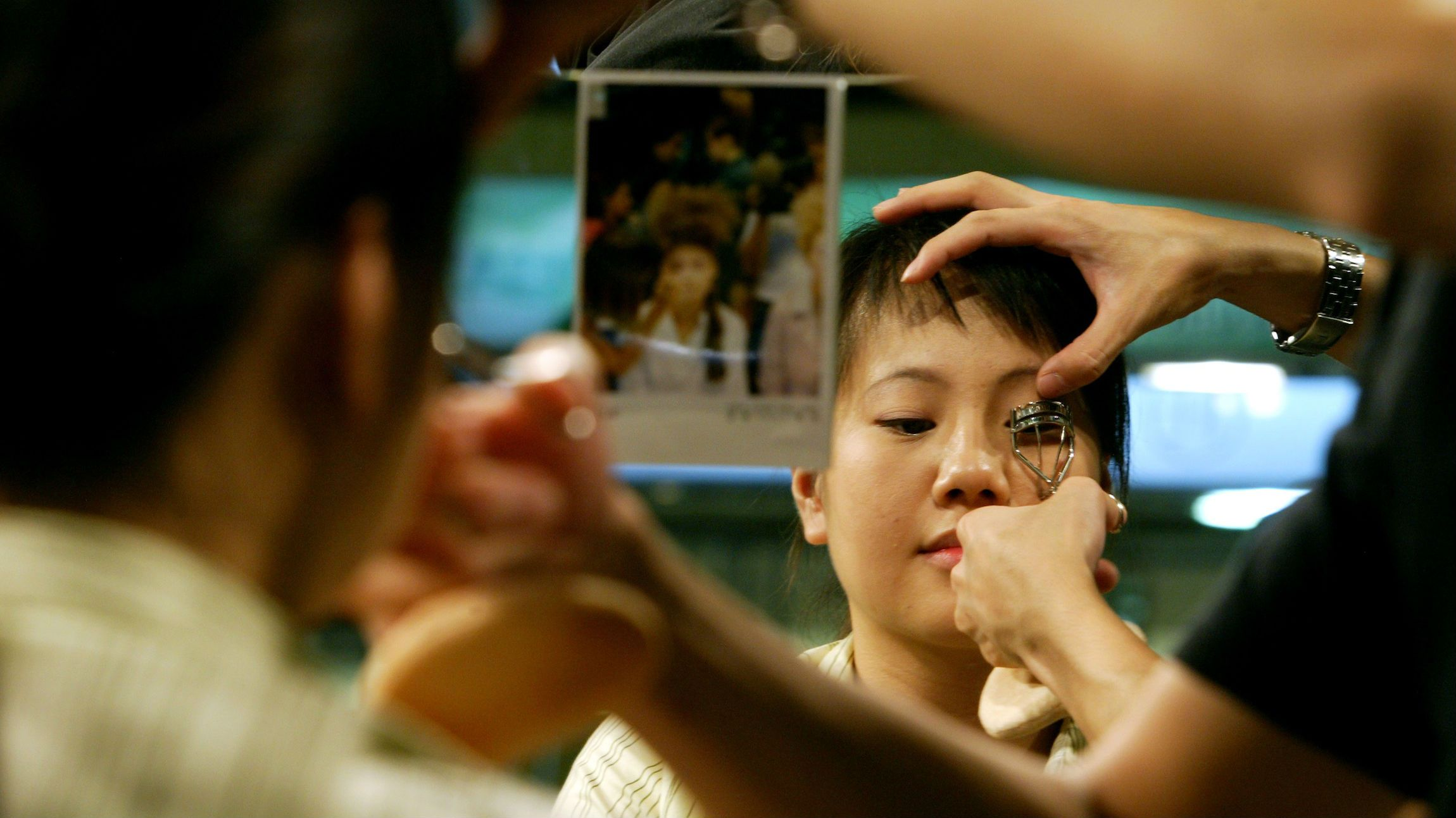 A make up artist works with a customer in Shanghai