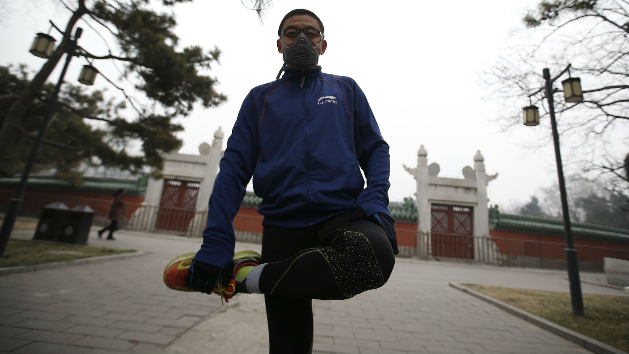 A man wears a mask in a park in Beijing where he goes jogging