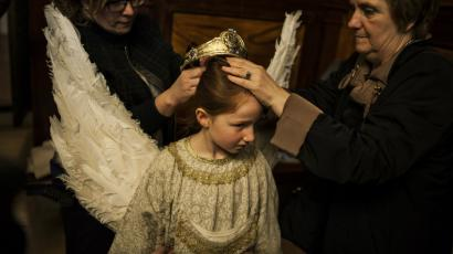 Relatives of eight-year-old Alba Oroz, center, adjust her crown during the Easter Sunday ceremony ''Descent of the Angel'', during Holy Week in the small town of Tudela, northern Spain.