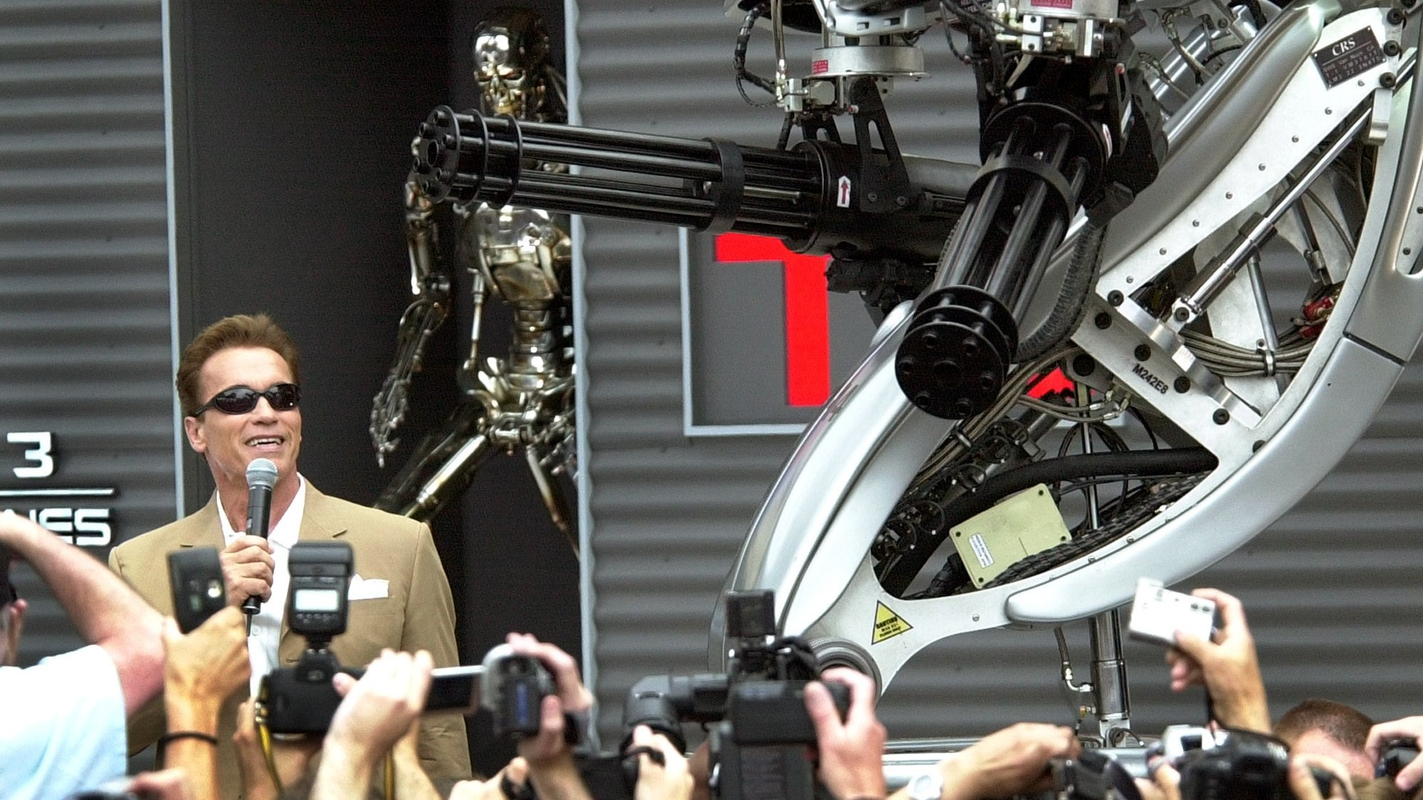 """Arnold Schwarzenegger, poses next to a robot for the promotion of his new film """"Terminator 3,""""directed by American Jonathan Mostow, on the sideline of the 56th Film Festival in Cannes, France, Saturday, May 17, 2003. (AP Photo/Patrick Gardin)"""