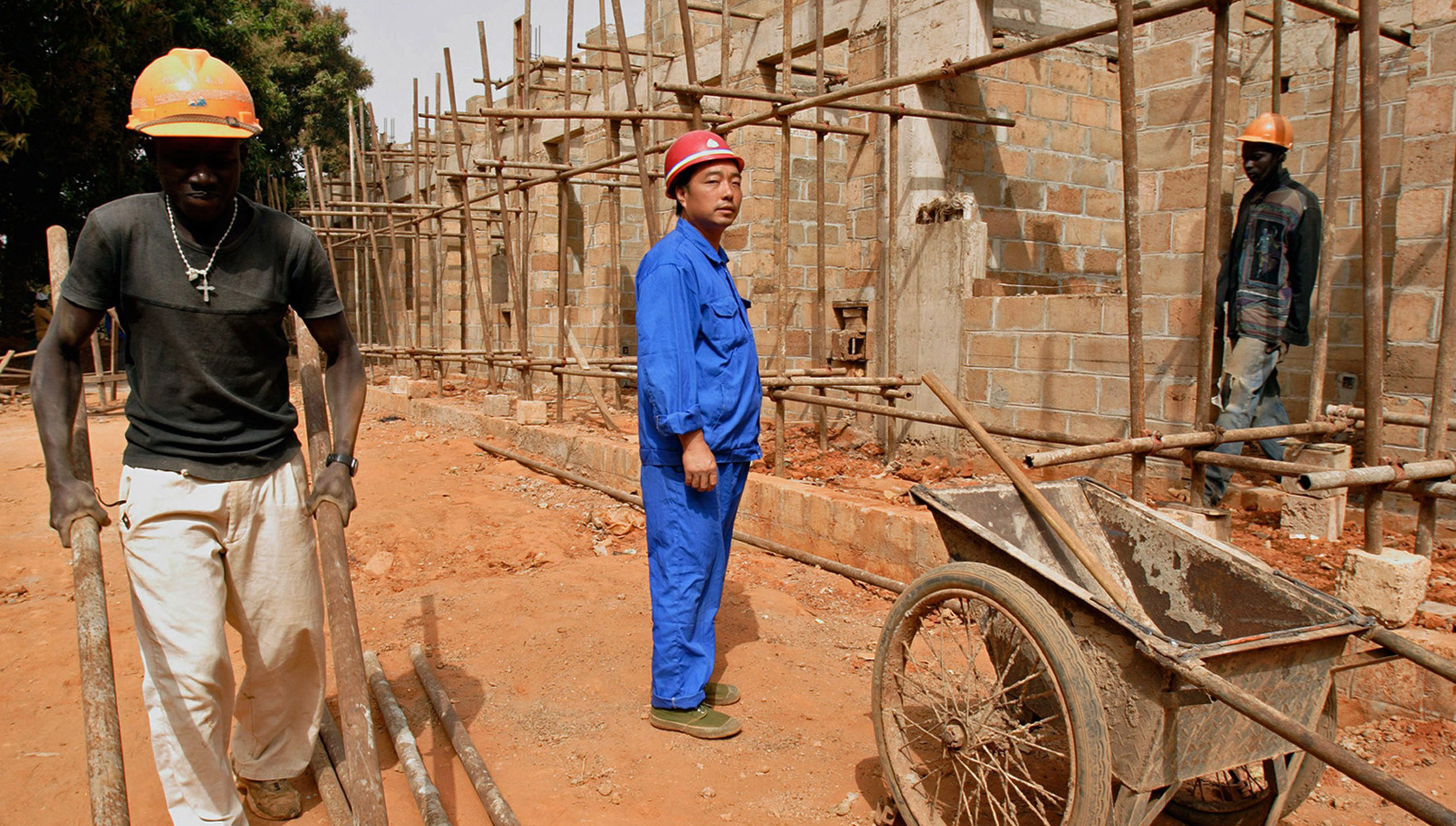 A Chinese foreman looks on as laborers work