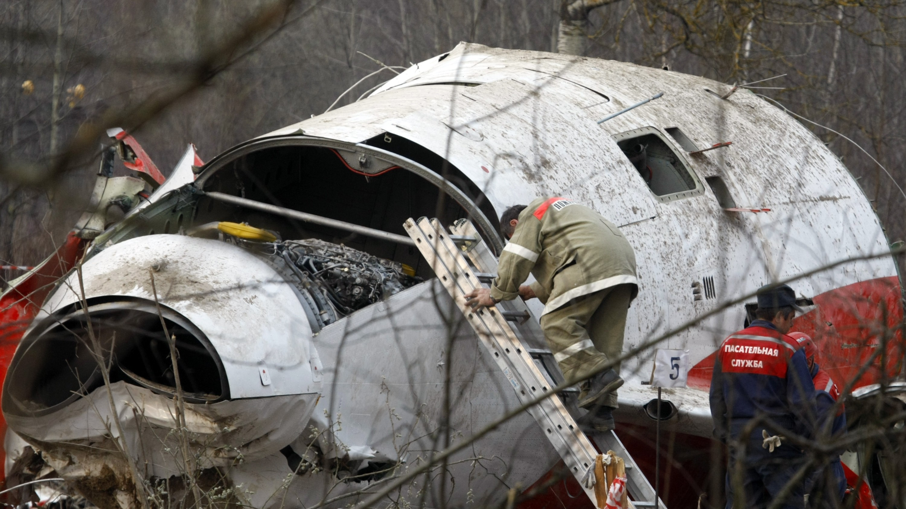 In this file photo dated Tuesday, April 13, 2010, showing unidentified Emergency ministry workers as they search through the wreckage of the Polish presidential plane is Smolensk, Russia, in which Polish President Kaczynski, his wife and some of the country's most prominent military and civilian leaders died. Russian Federal Investigative Committee said Tuesday, June 8, 2010, that four soldiers have been charged with stealing credit cards from the wreckage of the plane crash that killed Kaczynski and 95 others.