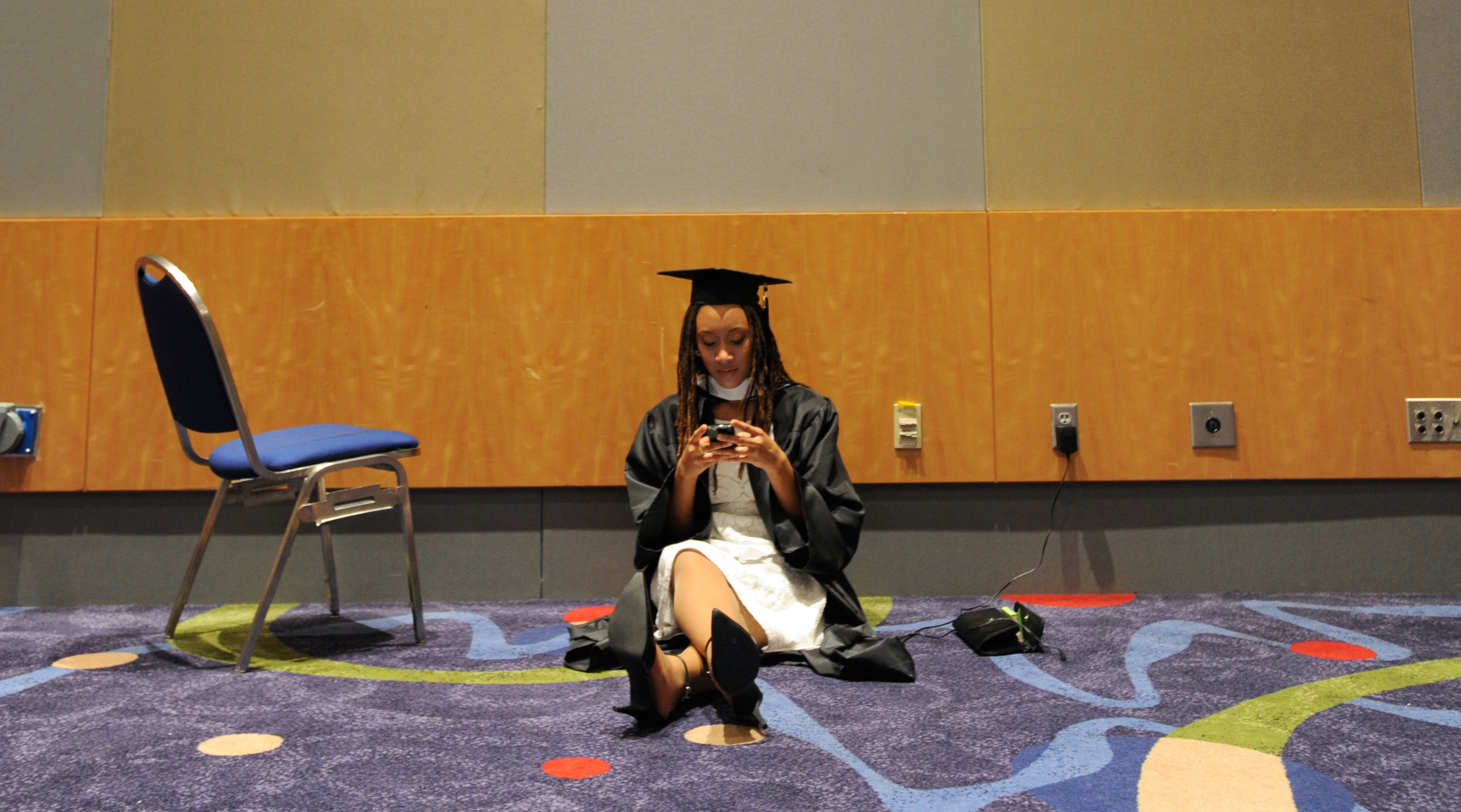 Spelman College graduating senior Vivian Aguayo, 20, of Silver Spring, Md., uses her mobile phone while waiting to participate in her commencement ceremony on Sunday, May 15, 2011, at the Georgia International Convention Center in College Park, Ga. First lady Michelle Obama is scheduled to deliver the commencement address to the graduates of Spelman College, and attendees had to arrive several hours early for security sweeps.