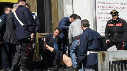 Rescuers and police help an injured person outside the tribunal building in Milan, Italy, after a shooting erupted inside a courtroom Thursday, April 9, 2015.