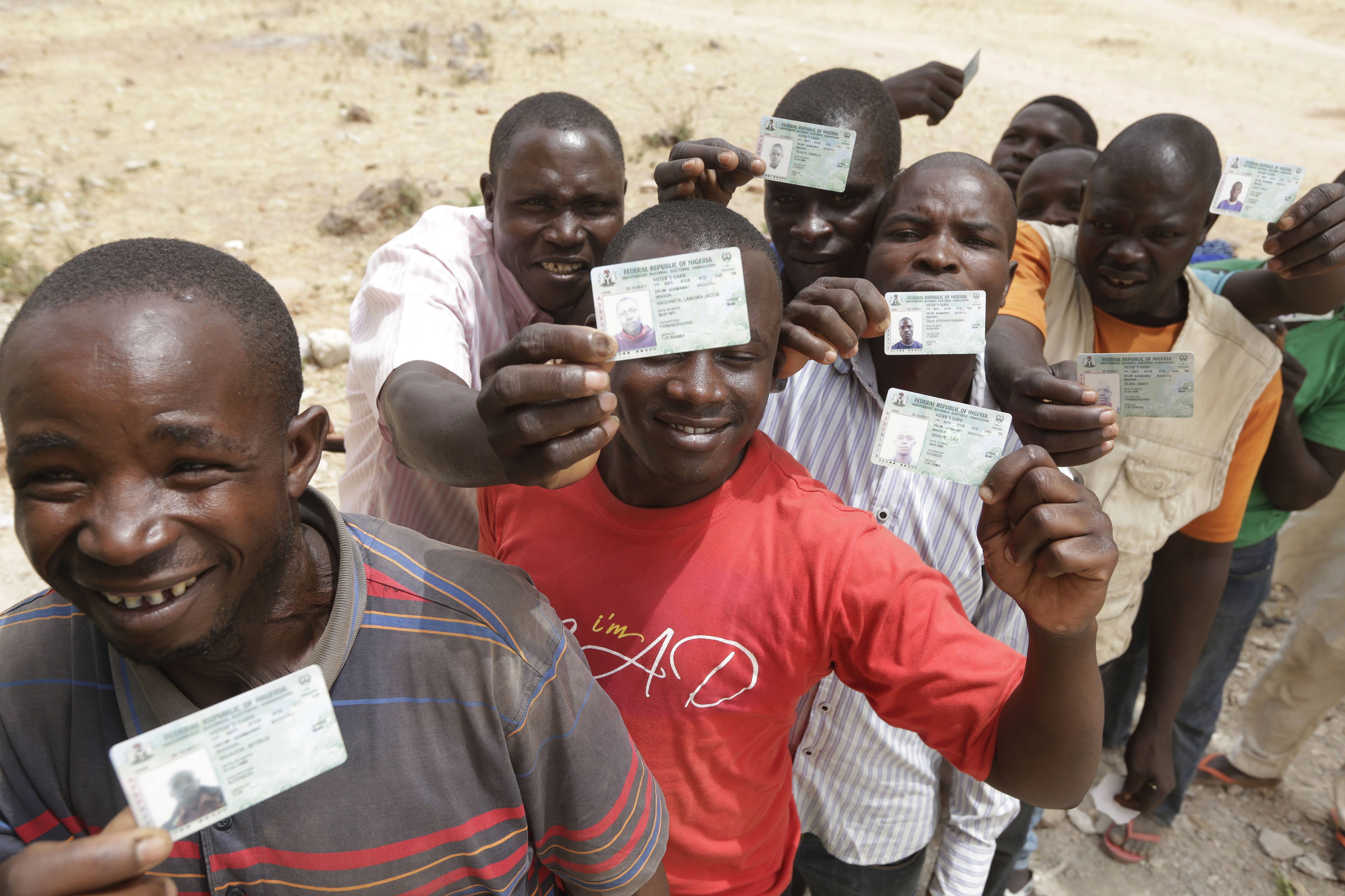 People displace by Islamist militants display their voters card