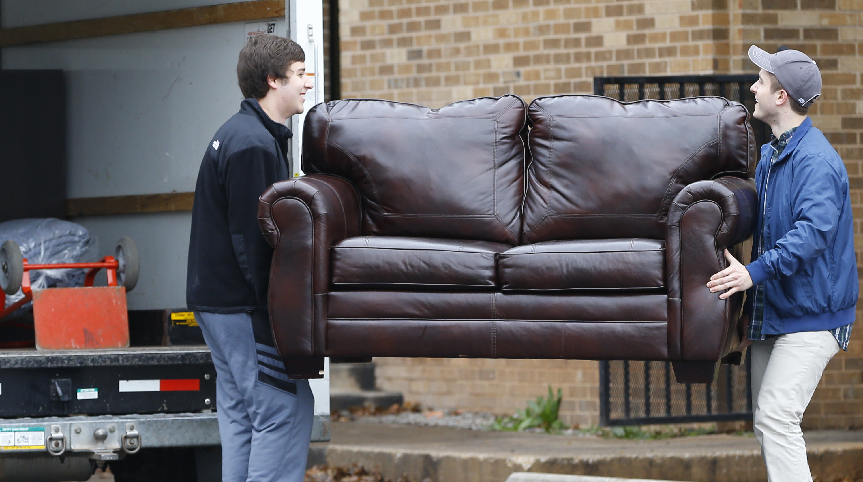 File-This March 10, 2015, file photo shows two men loading a couch from the now closed University of Oklahoma's Sigma Alpha Epsilon fraternity house into a moving truck, in Norman, Okla. Fraternities dominate social life at many American universities, but lately these organizations of male college students have been receiving unwanted attention for their bad behavior. At the University of Oklahoma, one prominent fraternity was shut down after members were caught on video performing a racist chant.