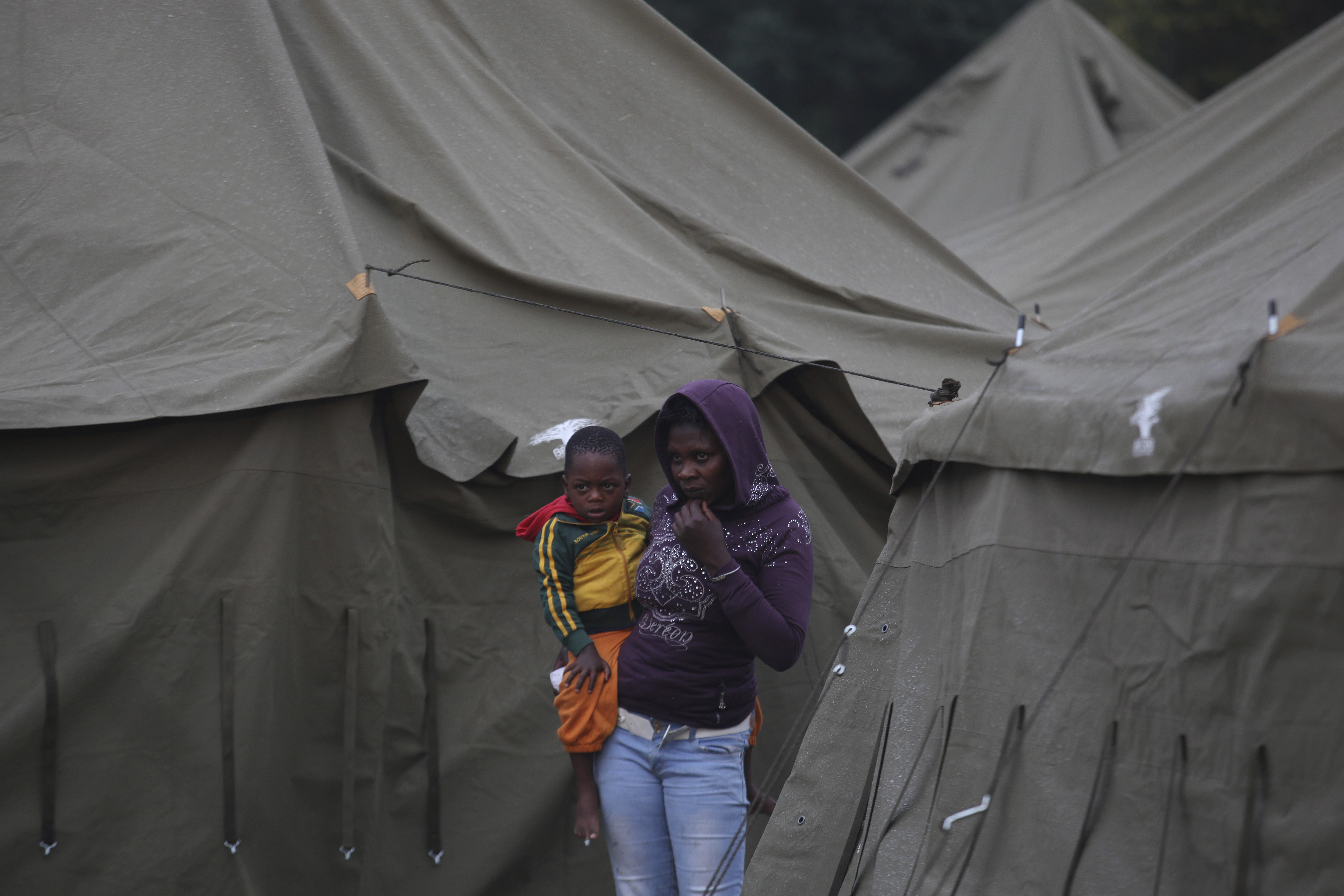 A woman carries her child at a temporary shelter set up for foreign nationals fleeing attacks from South Africans in and around Johannesburg Sunday, April 19, 2015. Mobs in South Africa attacked shops owned by immigrants in poor areas of the city overnight following similar violence in another part of the country that killed at least six people, according to media reports. (AP Photo/Denis Farrell)