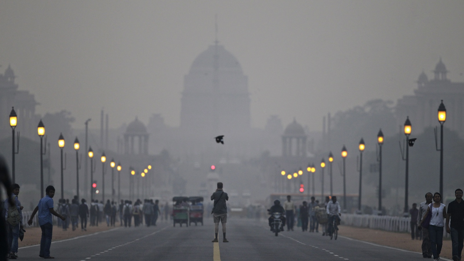 A tourist stands in the middle of a street in front of the Presidential Palace enveloped by a blanket of smog, caused by a mixture of pollution and fog, in New Delhi, India, Saturday, Nov. 3, 2012. Environmentalists say that the level of pollution in the city has reached an alarming level, according to news reports. (AP Photo/Altaf Qadri)