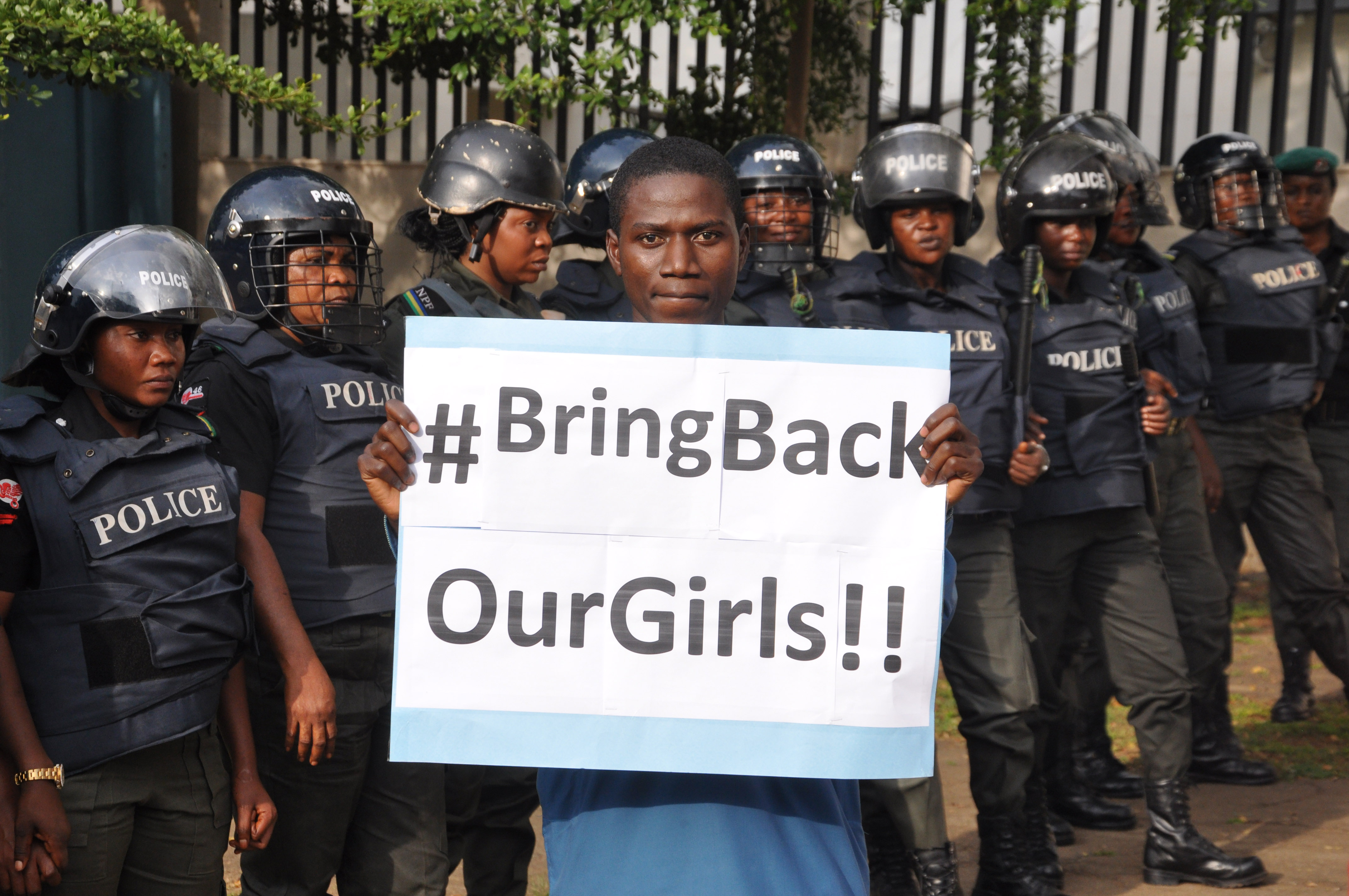 """A man poses with a sign in front of police officers in riot gear during a demonstration calling on the government to rescue the kidnapped girls of the government secondary school in Chibok, in Abuja, Nigeria, Tuesday, Oct. 14, 2014. Scores of protesters marched chanting """"Bring Back Our Girls"""" kidnapped six months ago by Boko Haram. (AP Photo/Olamikan Gbemiga)"""