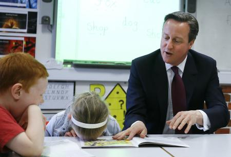 Britain's Prime Minister David Cameron reads a book to Lucy Howarth, 6, and Will Spibey, 5, left, during a visit to Sacred Heart RC primary school in Westhoughton near Bolton, England, Wednesday, April 8, 2015.