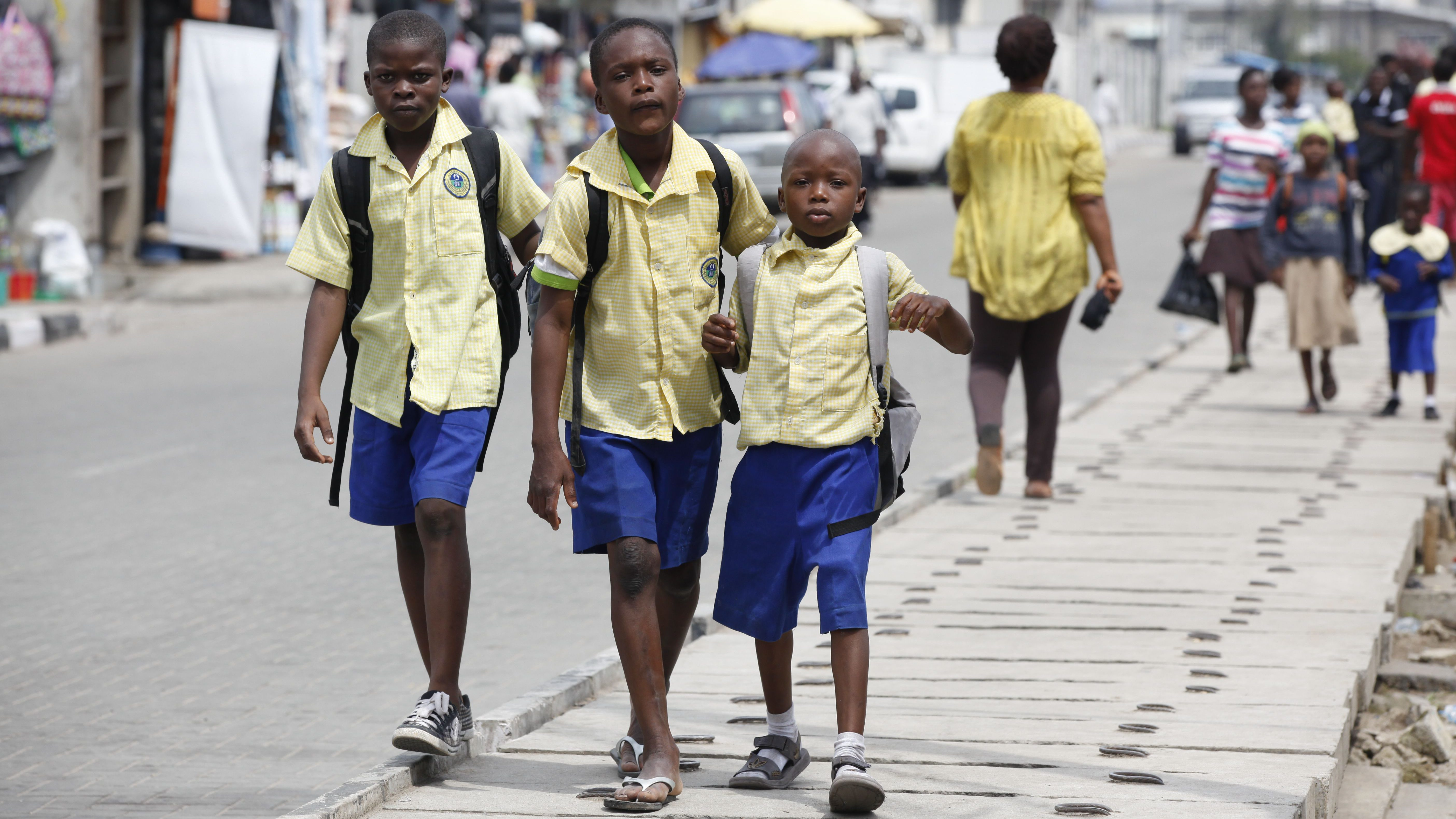 School children walk in the street in the Obalende area of Lagos, Nigeria, Tuesday, June 17, 2014. About 30 million primary school-aged children in sub-Saharan Africa are not in class, partially because of conflict and poverty, and progress to get them back to school has stalled, two U.N. agencies said. The situation is especially dire in West and Central Africa, which has the largest proportion of children out of school of any region in the world, said a pair of reports published Monday by UNICEF, the U.N. children's agency, and the statistics arm of UNESCO, the U.N. cultural and education agency. (AP Photo/Sunday Alamba)  (AP Photo/Sunday Alamba)