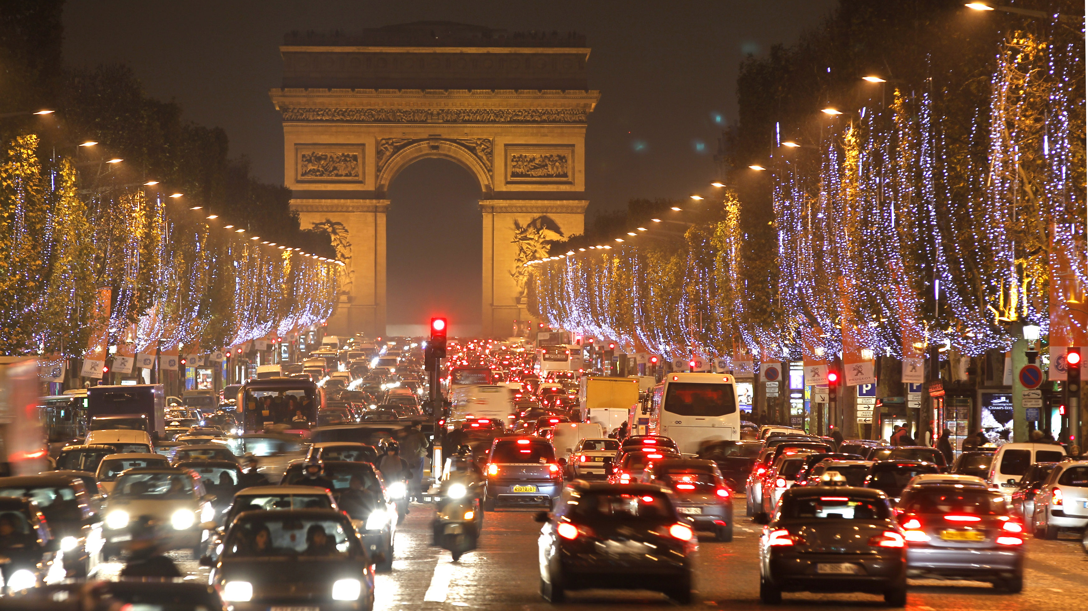 Holiday lights hang from trees to illuminate Champs Elysees in Paris as rush hour traffic fills the avenue leading up to the Arc de Triomphe November 22, 2010.
