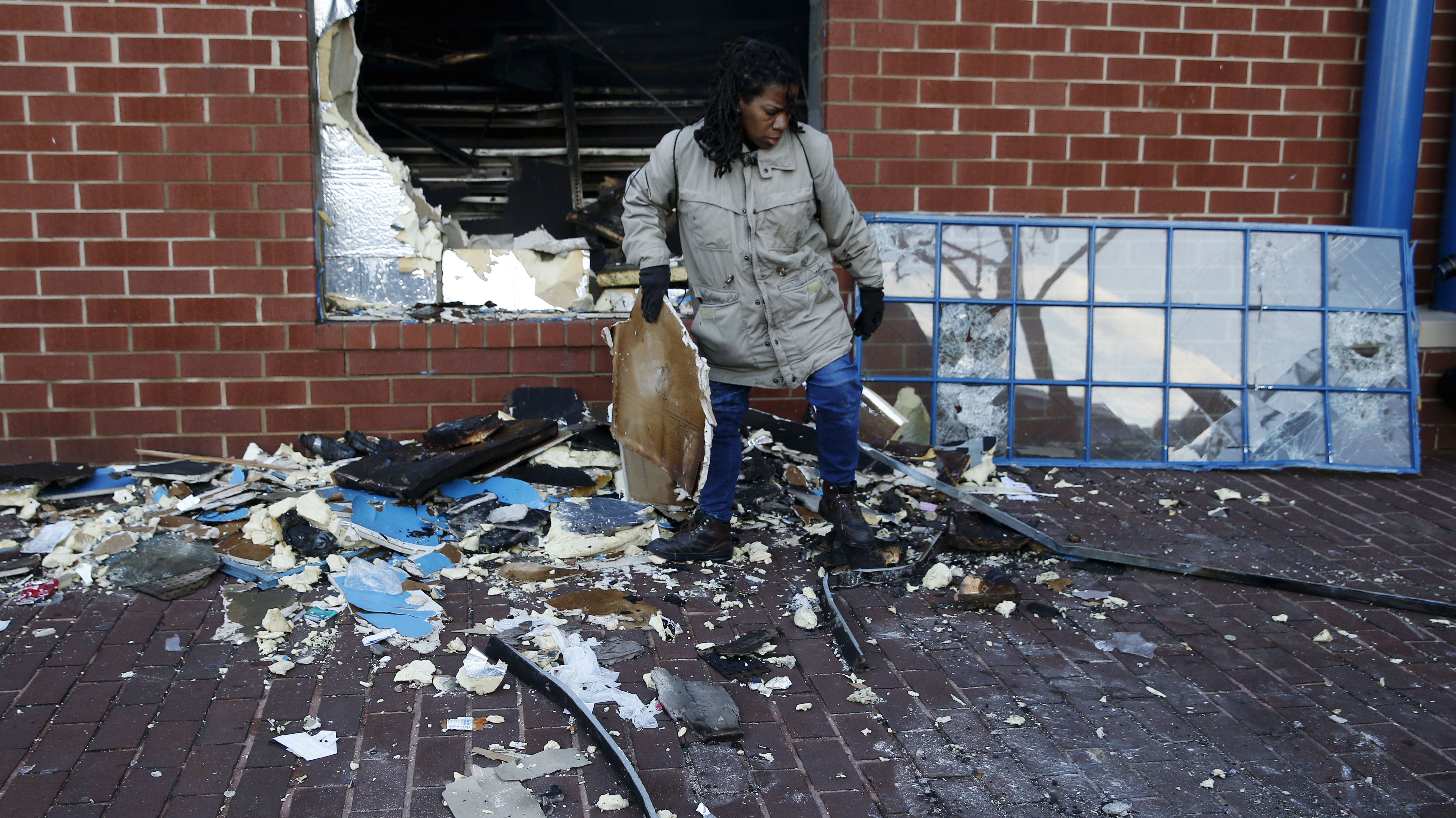 A woman cleans up a CVS store that was looted and set on fire during clashes with police on Monday in Baltimore, Maryland April 28, 2015. Baltimore erupted in violence on Monday as hundreds of rioters looted stores, burned buildings and at least 15 police officers were injured following the funeral of a 25-year-old black man who died after suffering a spinal injury in police custody. The riots broke out blocks from where the funeral of Freddie Gray took place and spread through much of west Baltimore.  REUTERS/Shannon Stapleton - RTX1AMY9