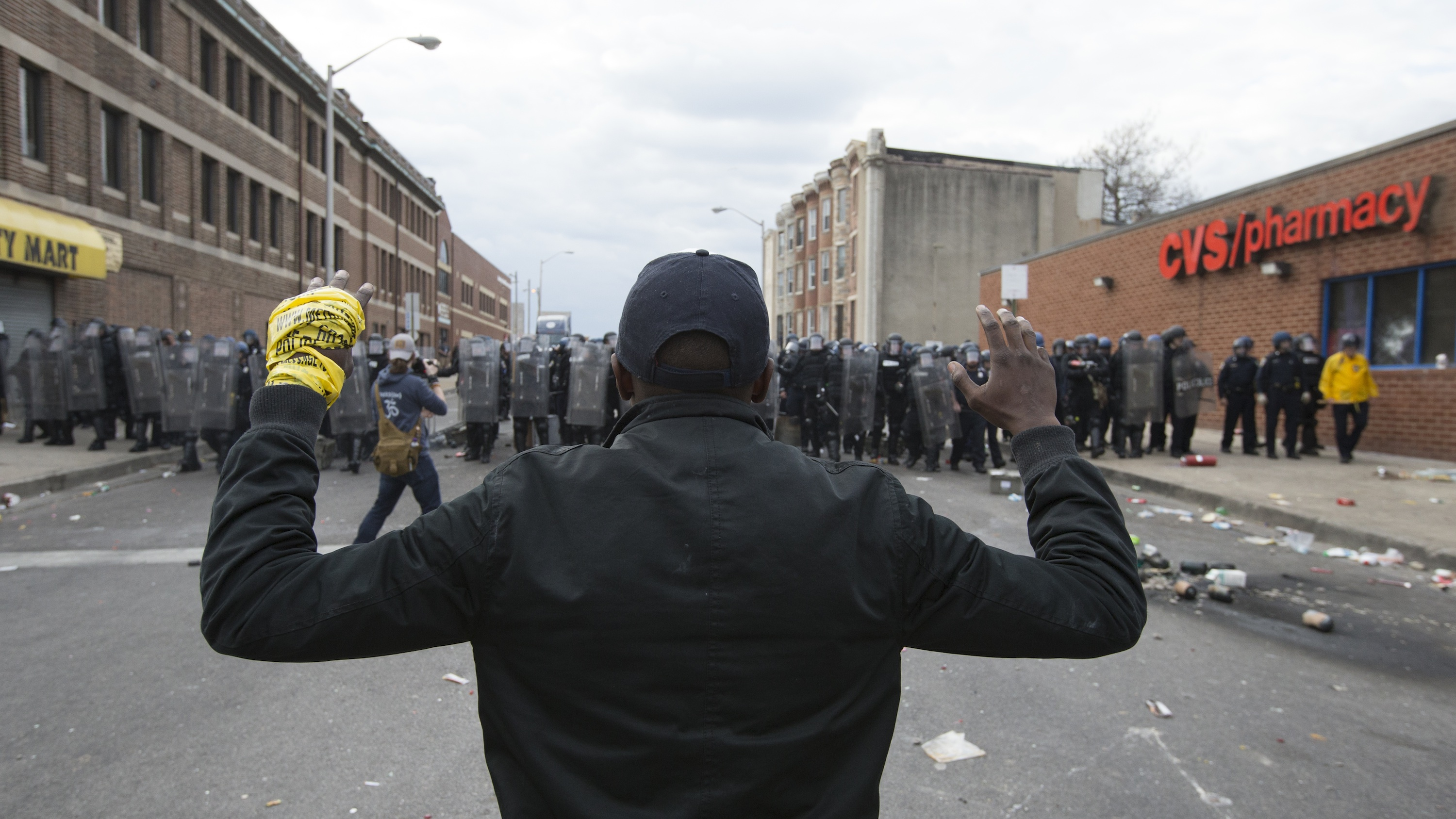 A youth stands in front of a police line as protests of the death of Freddie Gray continue, in Baltimore, Maryland, on April 27, 2015.