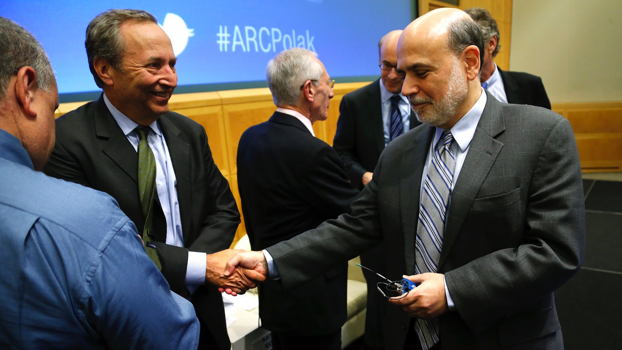 Harvard University President Emeritus Larry Summers (2nd L) shakes hands with U.S.Federal Reserve Chairman Ben Bernanke (R) after they participated in a panel discussion on financial crises during the International Monetary Fund (IMF) Jacques Polak Annual Research Conference in Washington, November 8, 2013. REUTERS/Jonathan Ernst (UNITED STATES - Tags: POLITICS BUSINESS)
