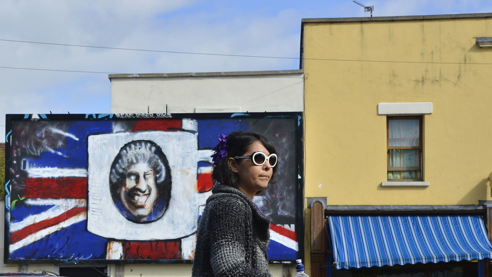 A pedestrian passes street art depicting Britain's Queen Elizabeth on a disused advertising hoarding in the St. Paul's area of Bristol, south west England May 16, 2012.   REUTERS/Toby Melville (BRITAIN - Tags: CITYSPACE SOCIETY ROYALS) - RTR3250E