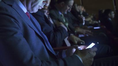 People listen and check their phones as United States Secretary of State John Kerry speaks during a 2014 meeting for Climate Week New York.