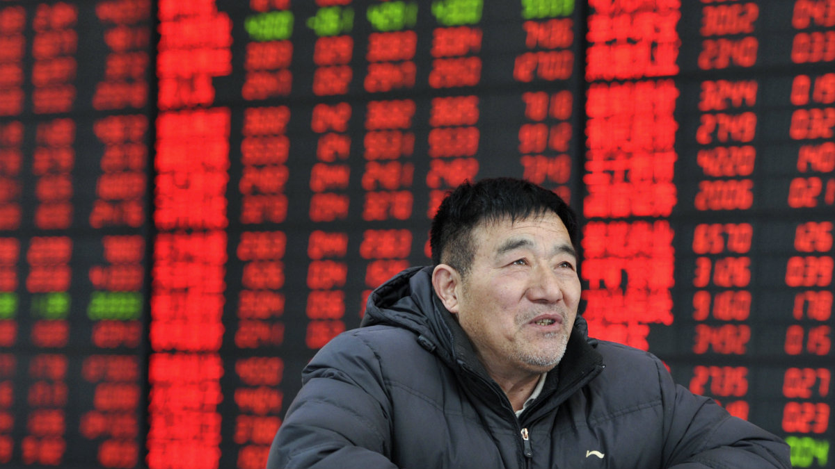 An investor looks on in front of an electronic board showing stock information at a brokerage house in Fuyang, Anhui province.