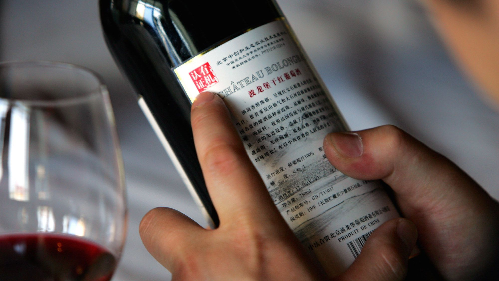 **ADVANCE FOR SUNDAY, AUG. 7** A wine novice reads information on bottle of Chinese red Chatteau Bolongbao on the vineyards grounds on the foothills of Mount Wulan in Cheng Guan, Fangshan district south of Beijing, May 26, 2005. For the Chinese, alcohol long meant beer or Chinese wine, which is made from grain rather than grapes.But spreading prosperity is changing drinking habits. Local and foreign vintners say the Chinese are increasingly interested in grape wines. (AP Photo/Elizabeth Dalziel)