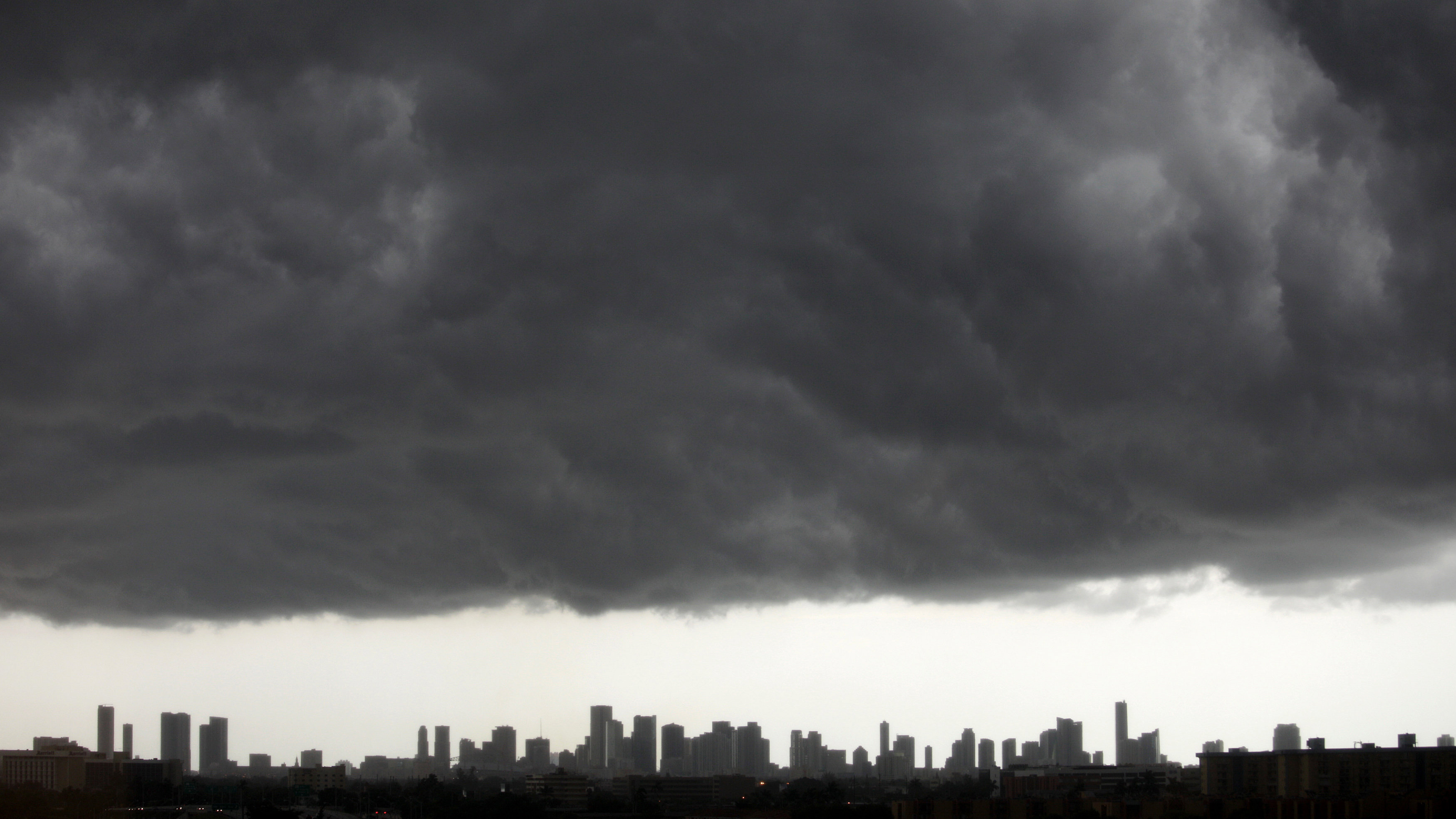 Dark clouds pass over downtown Miami, Florida August 15, 2010. An area of low pressure over southwest Georgia could move southward into Gulf of Mexico waters by early Monday and has a medium chance of becoming a tropical cyclone in the next 48 hours, the National Hurricane Center said on Sunday. The low pressure area was the remnant of Tropical Depression Five which dissipated on Wednesday in the Gulf. The U.S. Gulf of Mexico is home to about 30 percent of U.S. oil production, 11 percent of natural gas production, and more than 43 percent of U.S. refinery capacity.