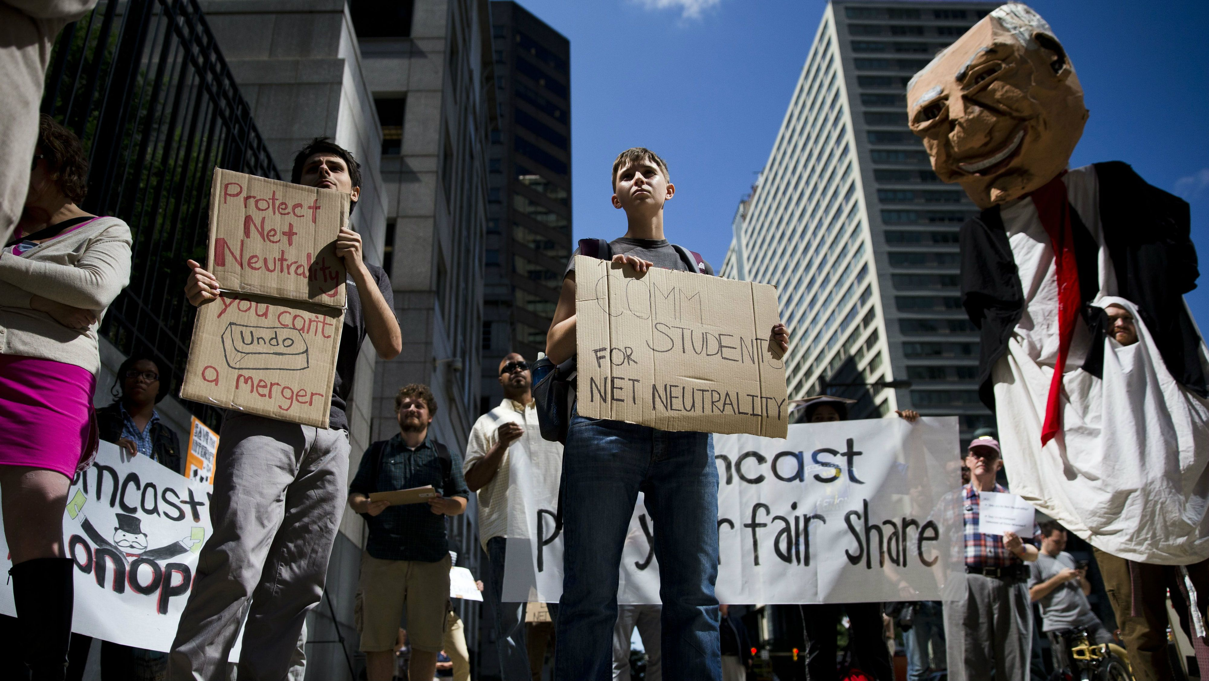 Protesters demonstrate across the street from the Comcast Center Monday, Sept. 15, 2014, in Philadelphia.