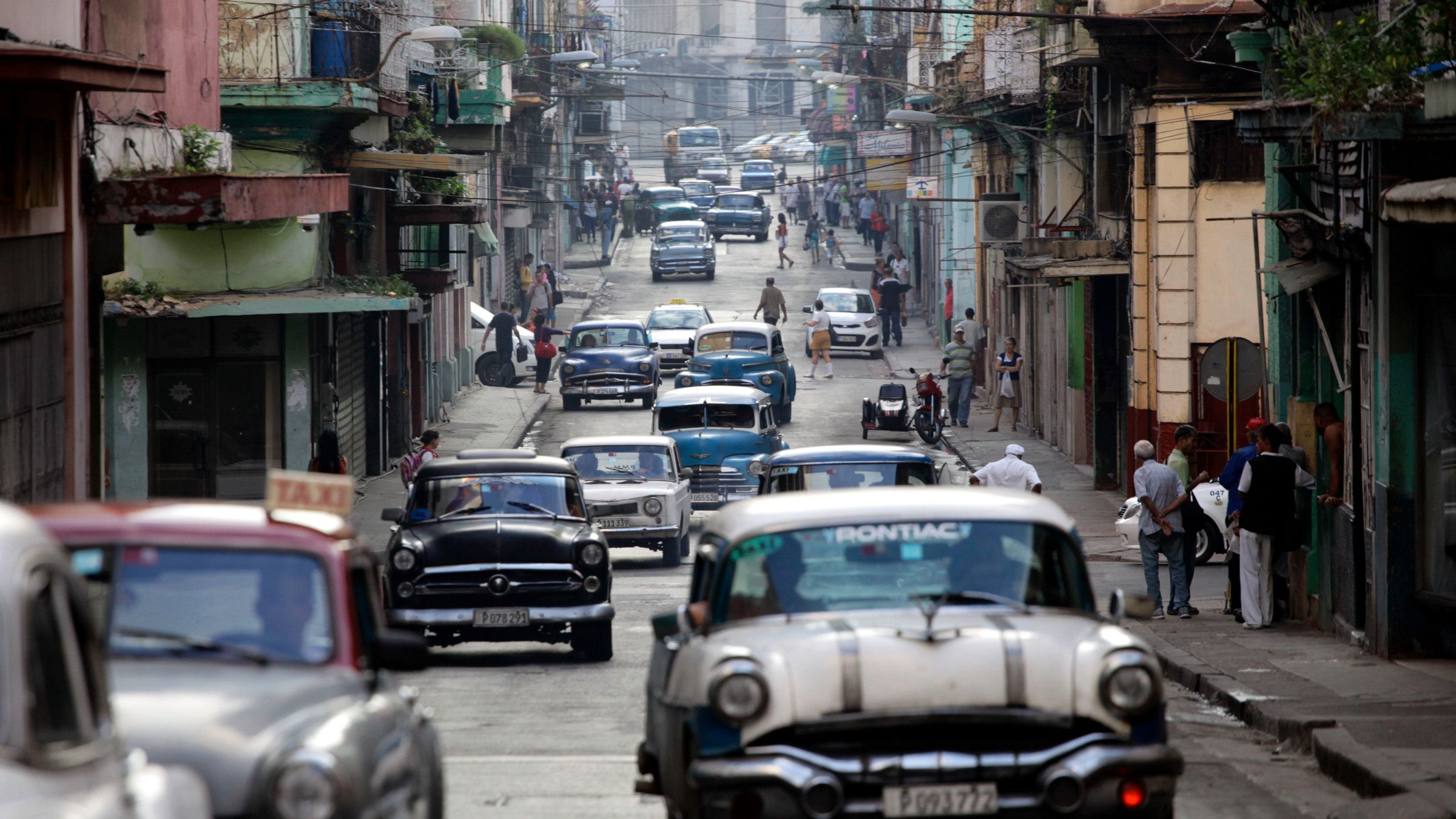 Classic American cars used as collective taxis drive along a street in Havana, Cuba, Friday, Jan. 16, 2015. Tens of thousands more American tourists are expected to flock this year to a country where some five-star hotels don't have working air-conditioning or hand towels. The Obama administration hopes the new wave of U.S. tourists will fuel one of the healthiest parts of Cuba's new entrepreneurial sector, the thousands of private bed and breakfasts.