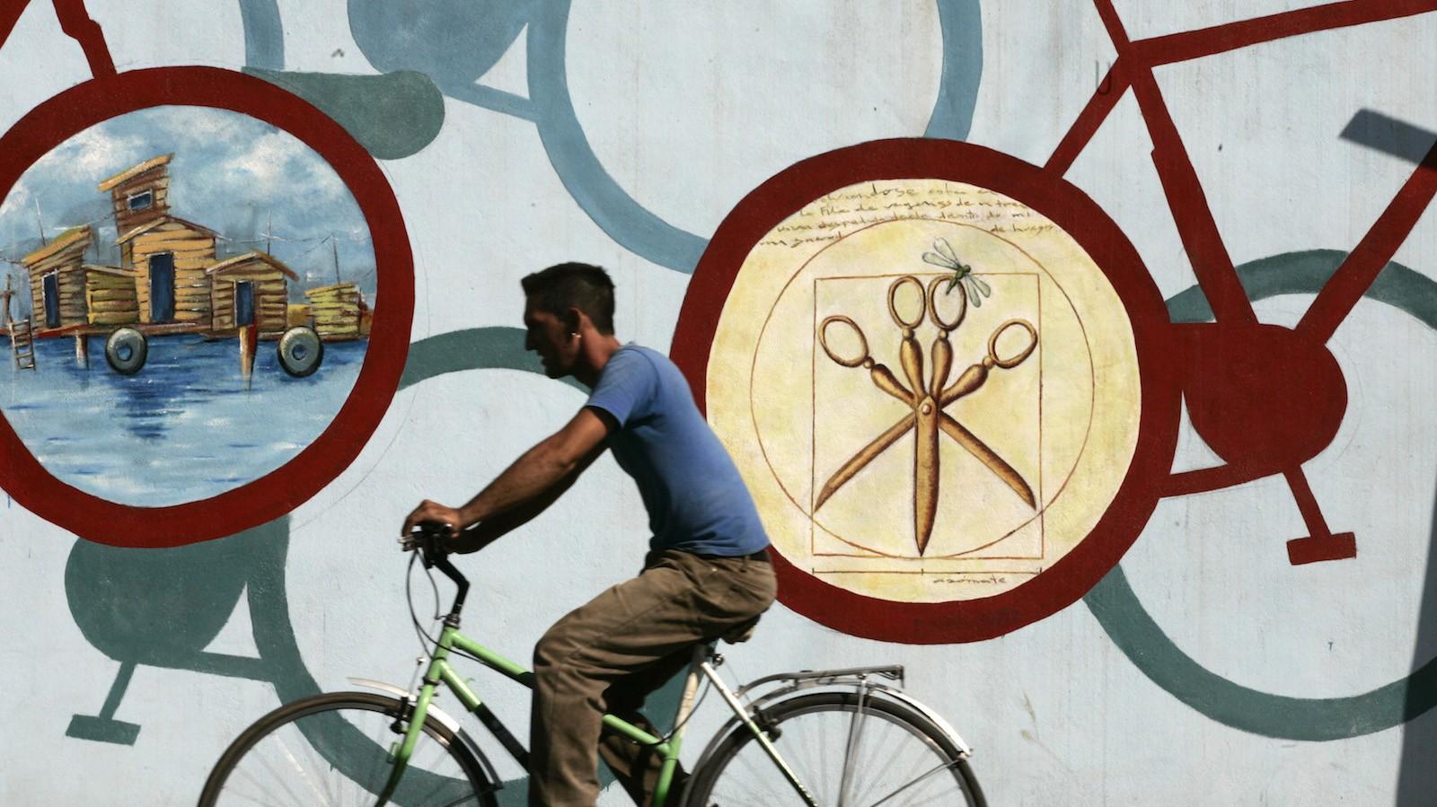 A man rides his bicycle past a wall painting in Cienfuegos, Cuba, November 9, 2007. REUTERS/Enrique De La Osa (CUBA) - RTX60D