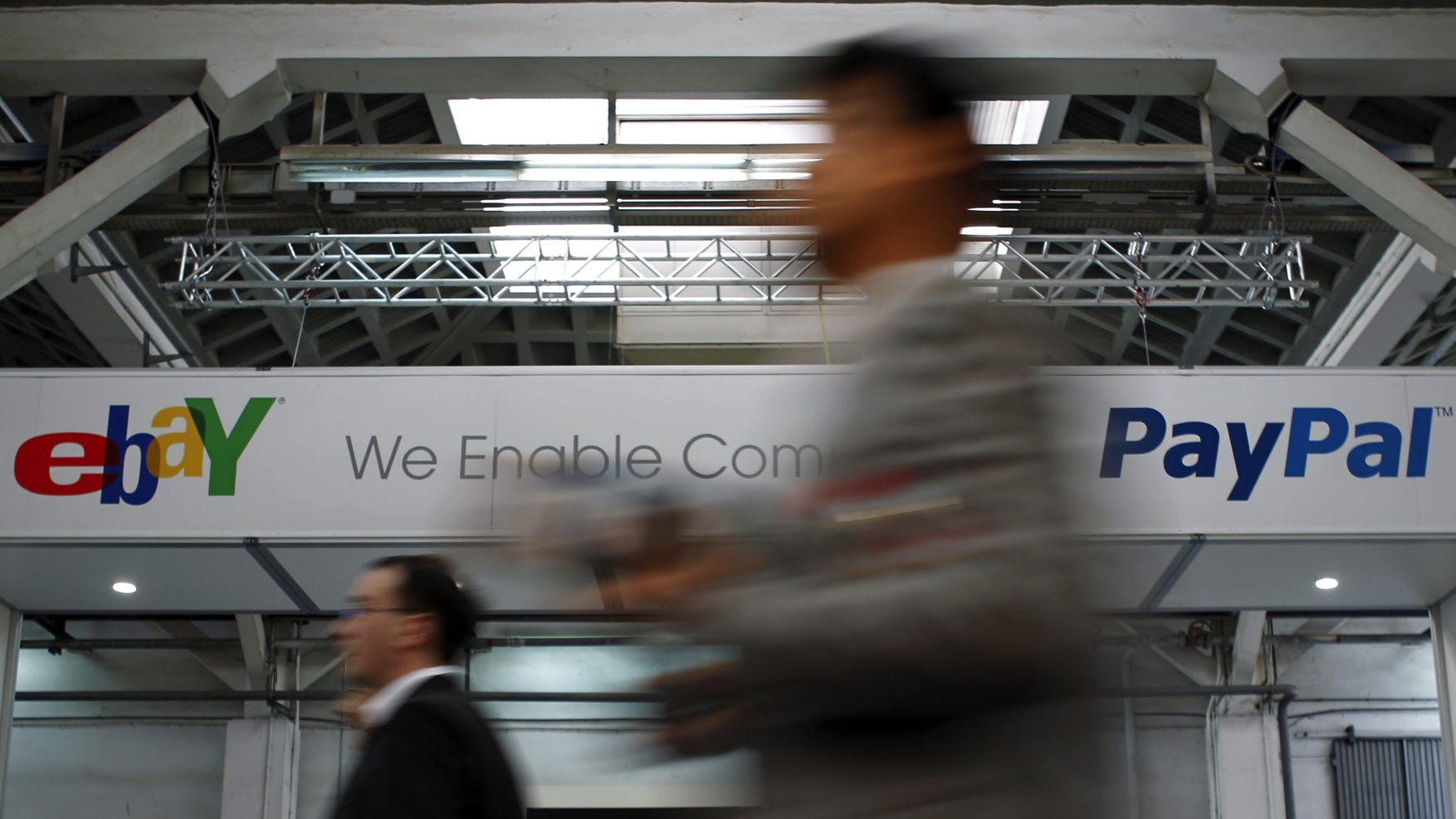Visitors walk past an Ebay and PayPal banner at the Mobile World Congress in Barcelona February 28, 2012. The GSMA Mobile World Congress, representing the interests of the worldwide mobile communications industry, will take place from February 27 to March 1 in Barcelona.